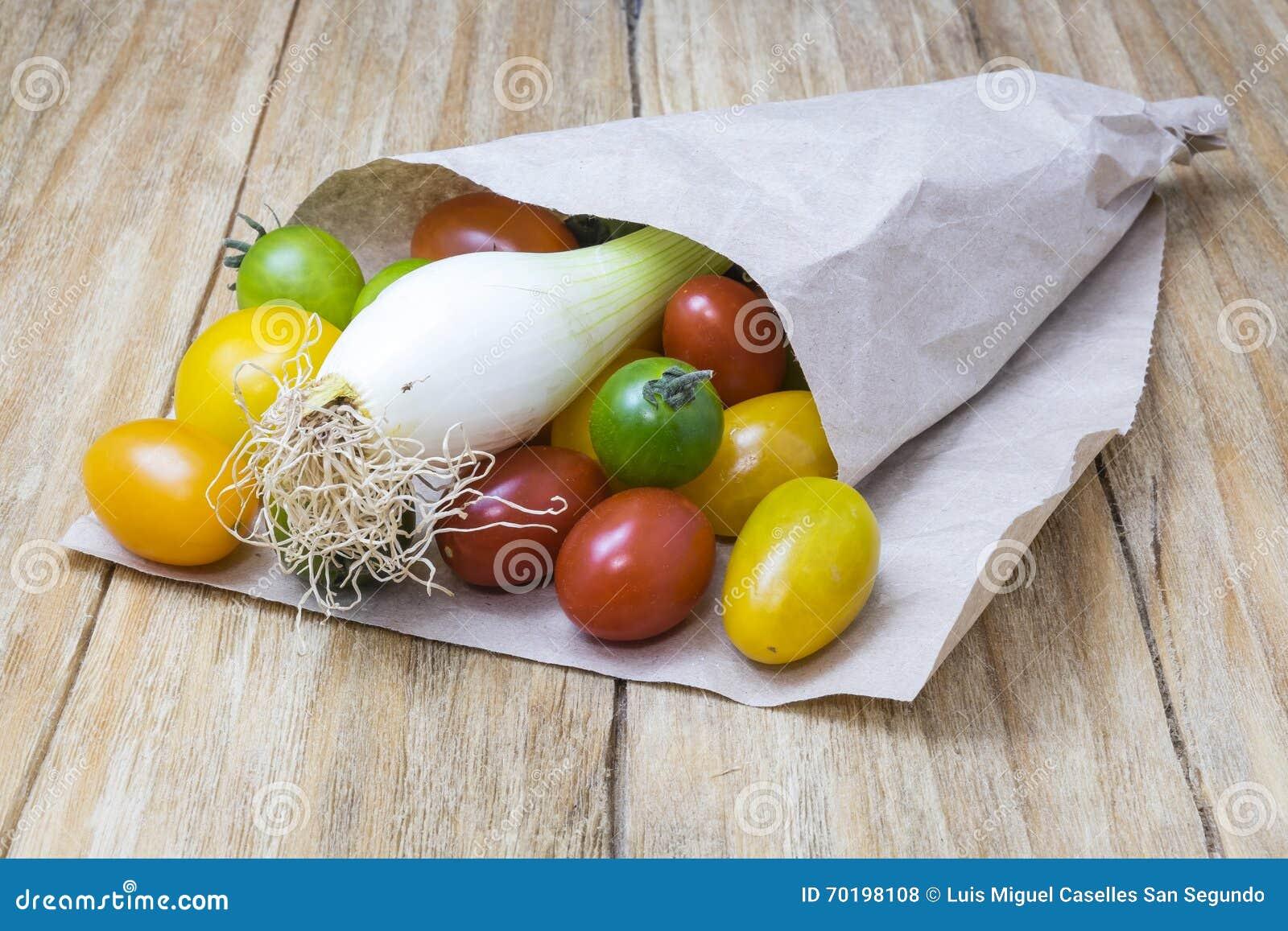 Röda tomater, gulingar, gräsplaner och salladslökar
