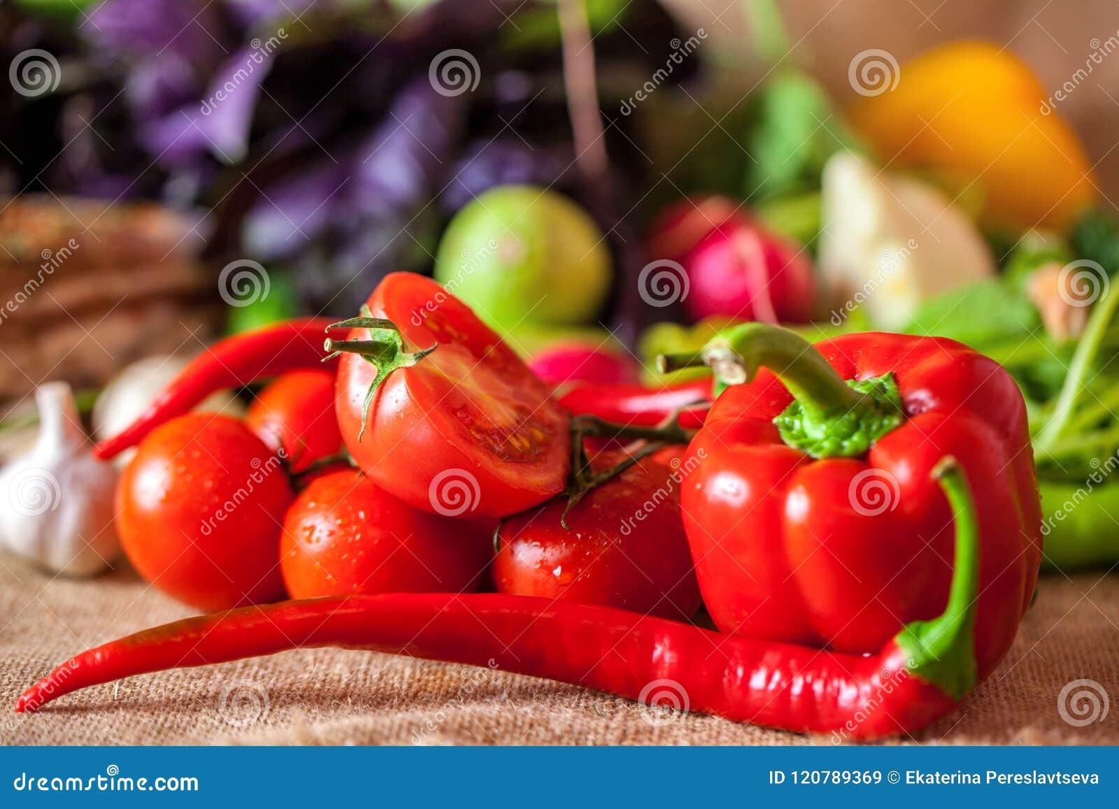 Röda tomater och mogen röd peppar med vattendroppar, sunt matbegrepp