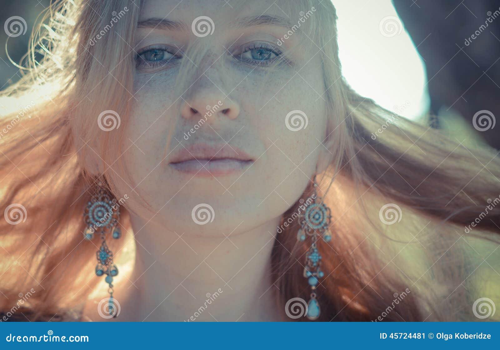 Rödhårig flicka med fräknar i örhängen,