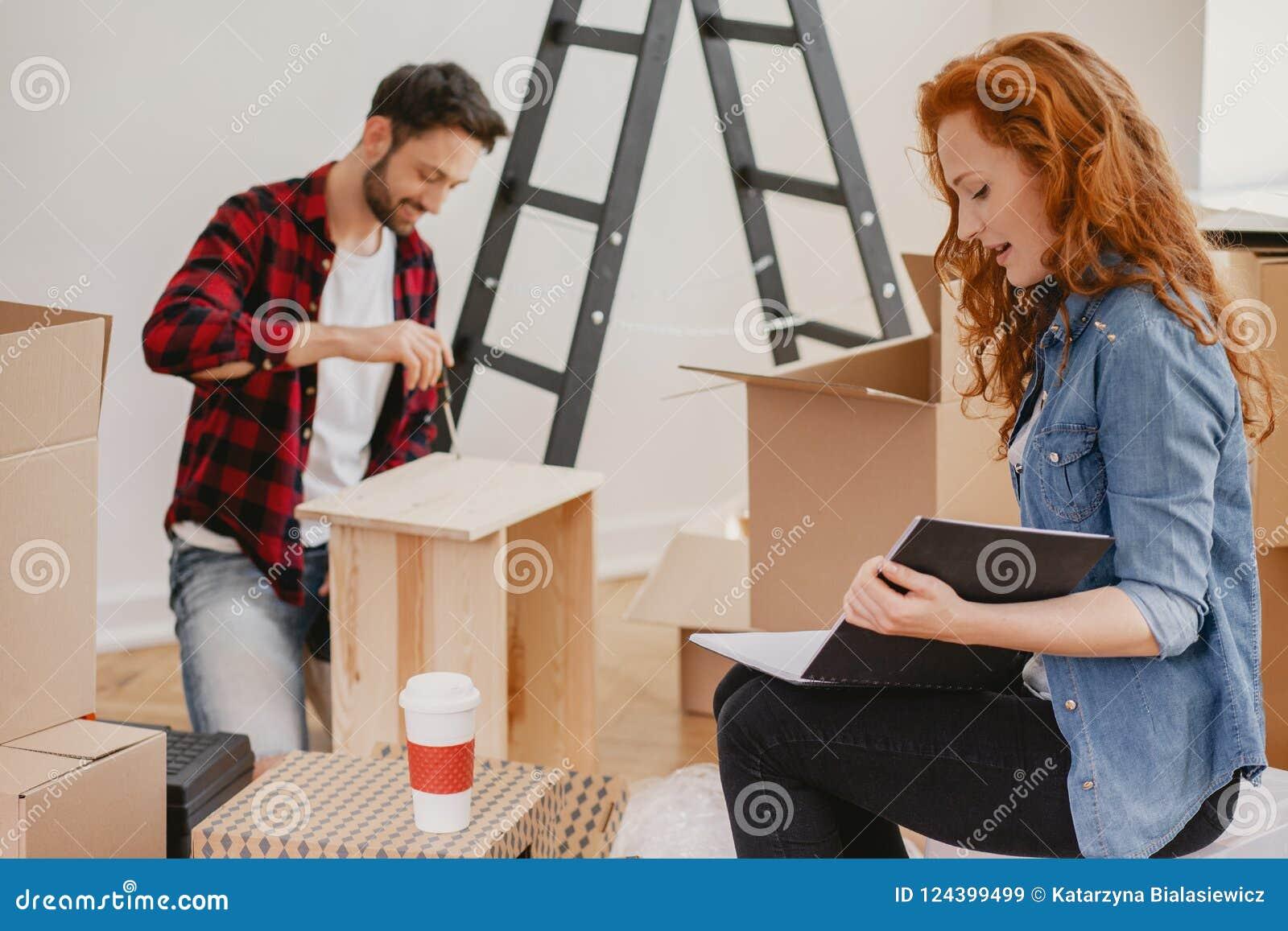 Rödhårig kvinna som ser fotoalbumet, medan möblera en lägenhet
