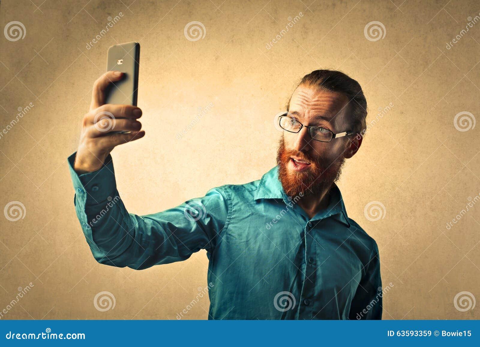 Rödhårig man som gör en selfie