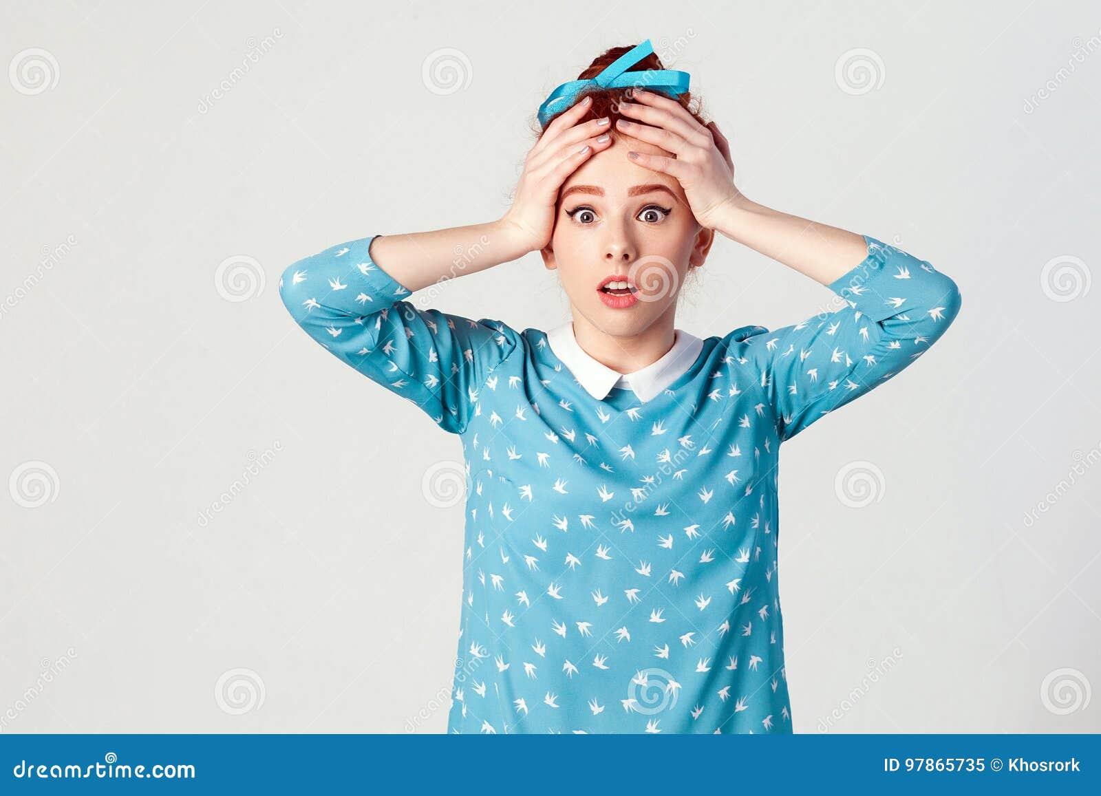 Rödhårig manflicka som ser desperat, och nöd och att rymma händer på hennes huvud som skriker med den öppna munsneda bollen