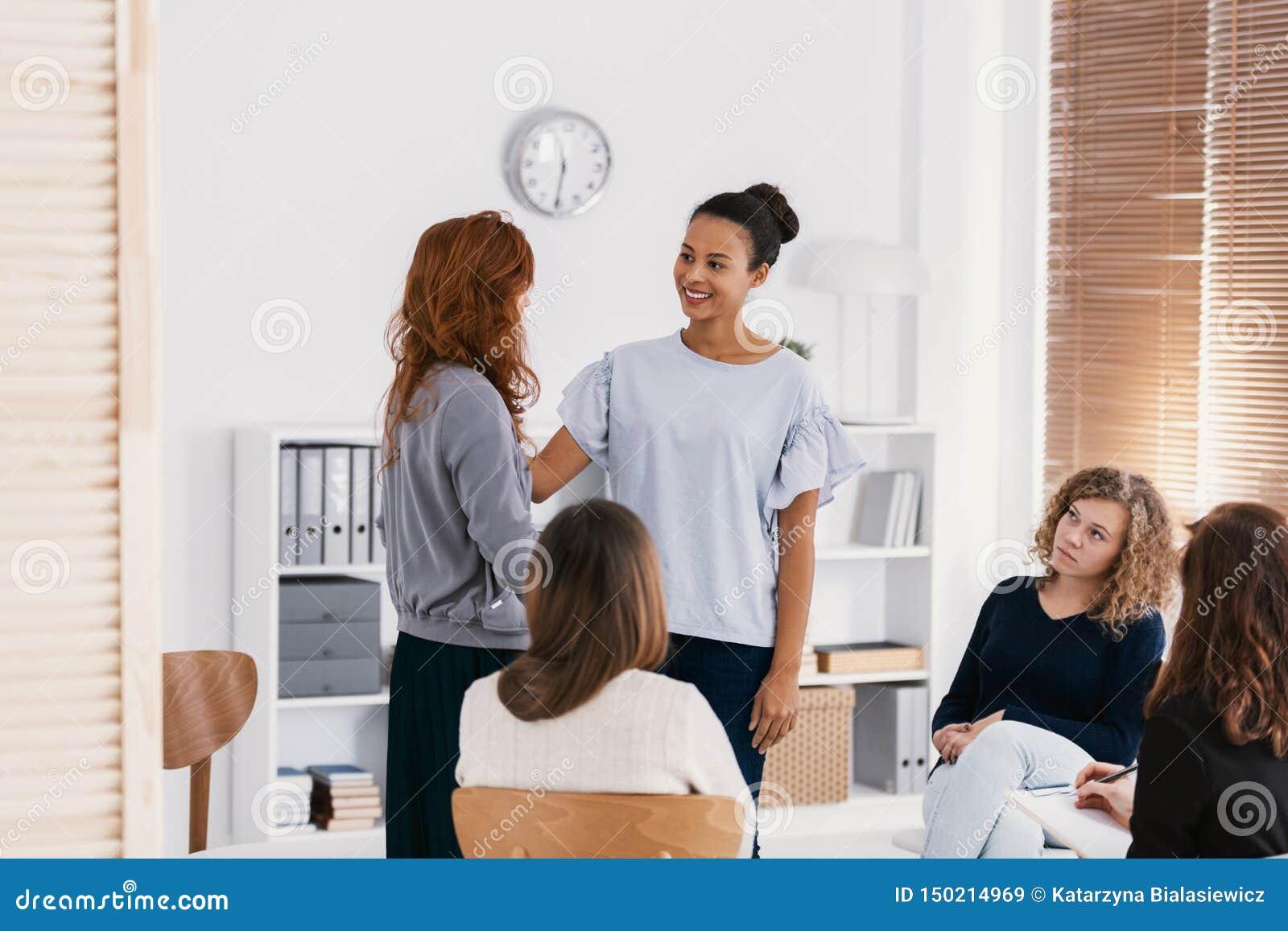 Rödhårig mankvinna som stöttar den ledsna vännen under psykoterapigruppmöte