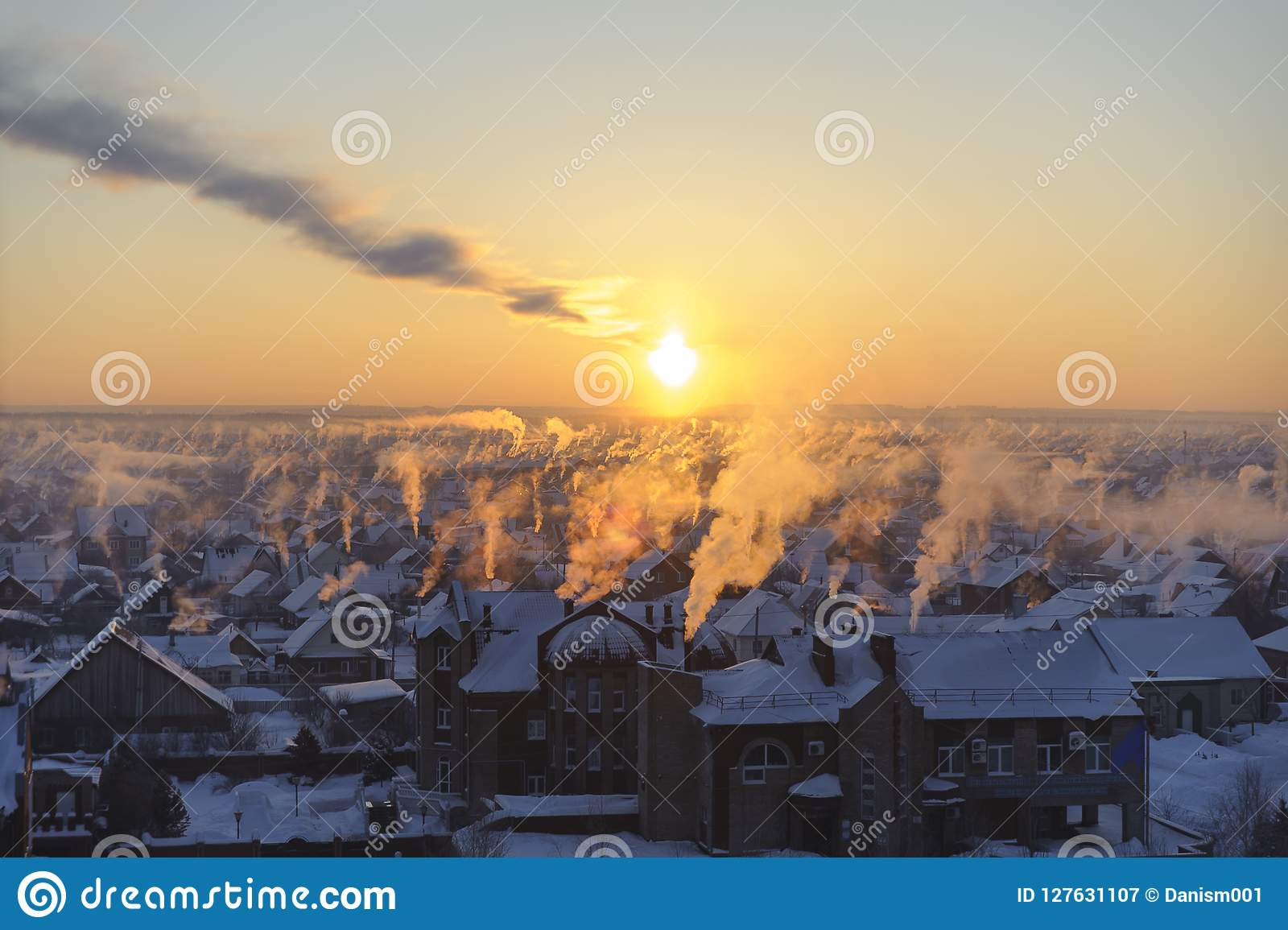Rök på den frostiga solnedgången