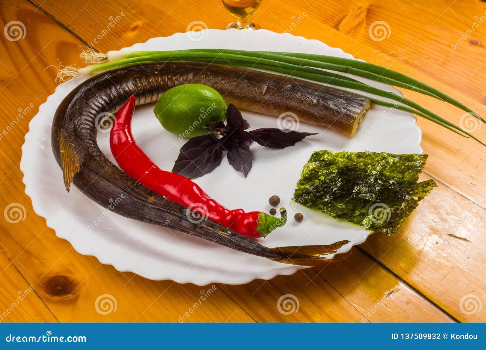 Rökt garfish med limefrukt, basilika, salladslökar, chili, norichiper, kryddor, olivolja i en vit keramisk maträtt, på en trätabe