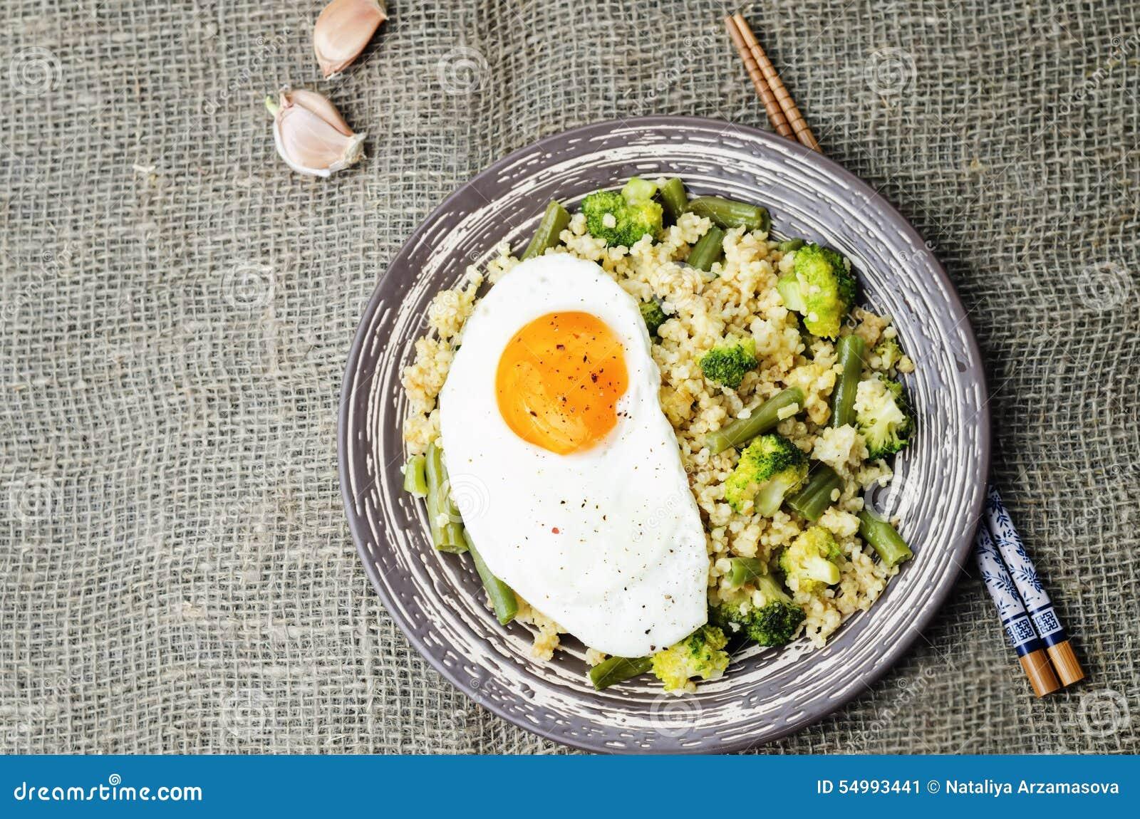 Rör stekt hirs med broccoli, haricot vert och det stekte ägget