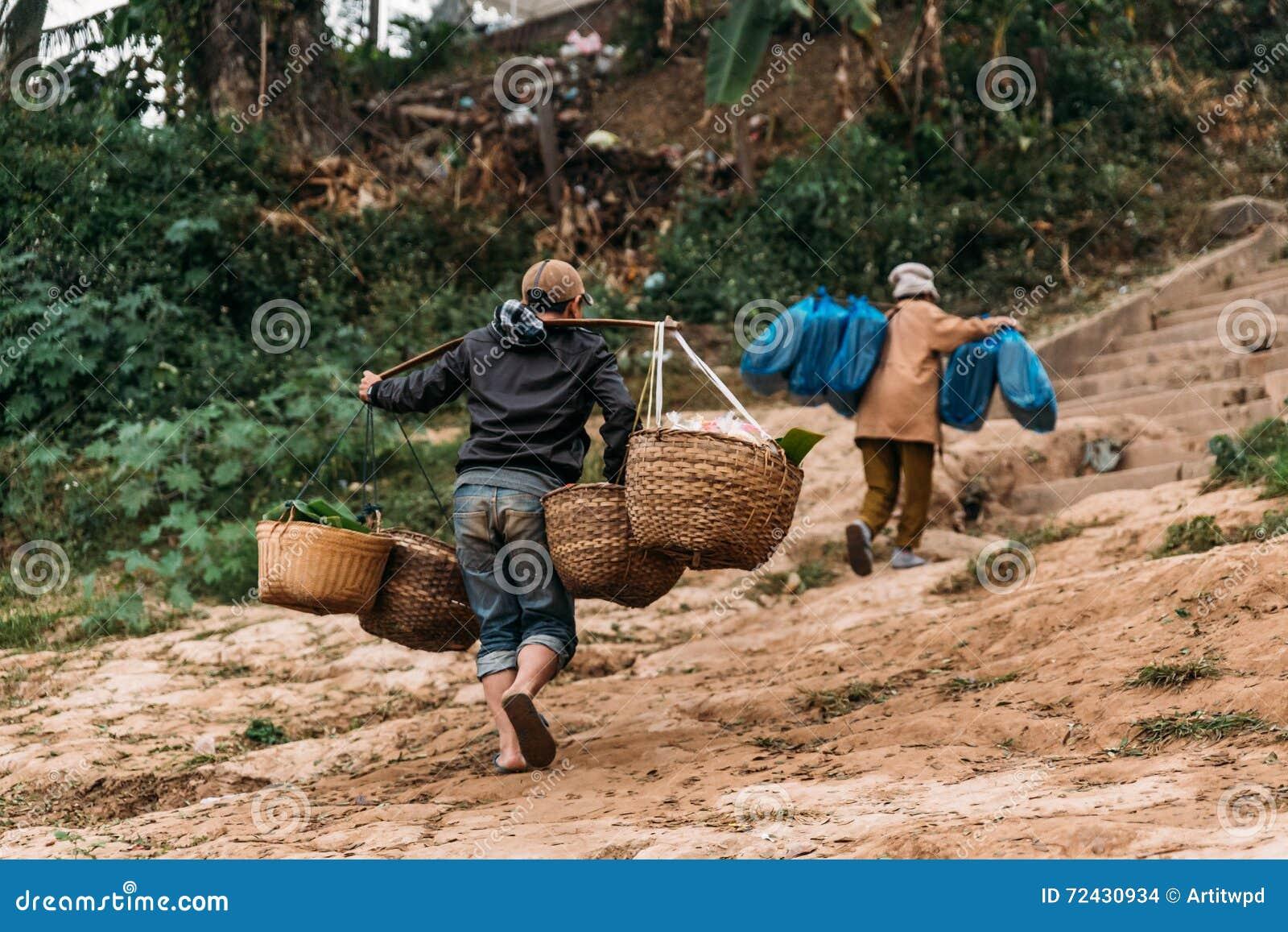 Rörande artiklar för folk till landet med fartyget i floden på Luang Prabang, Laos