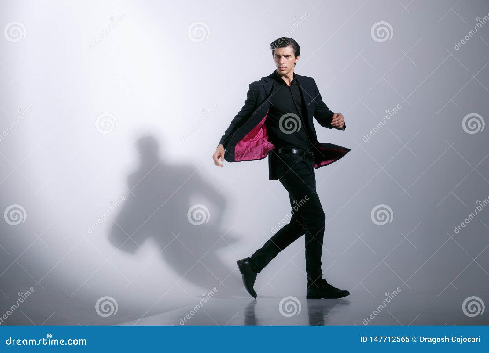Rörelsebild av en attraktiv stark oavkortad elegant svart dräkt för ung man som isoleras på en vit bakgrund