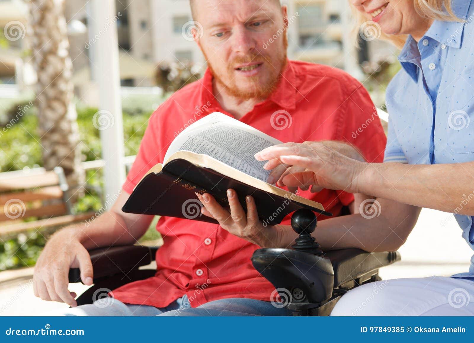 Rörelsehindrad man som studerar den heliga bibeln