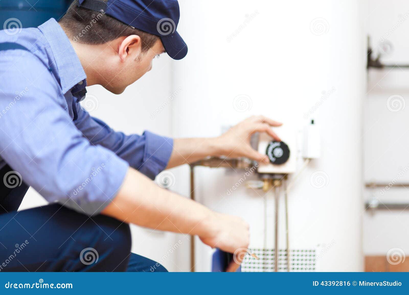 Rörmokare som reparerar en varmvattenvärmeapparat