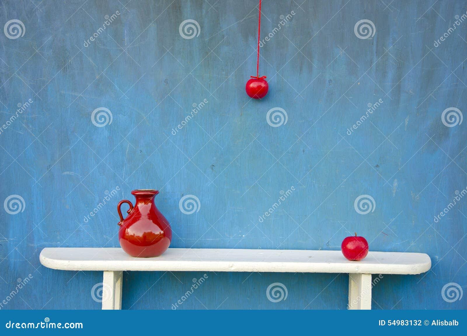 Rött äpple och röd vas på den vita hyllan