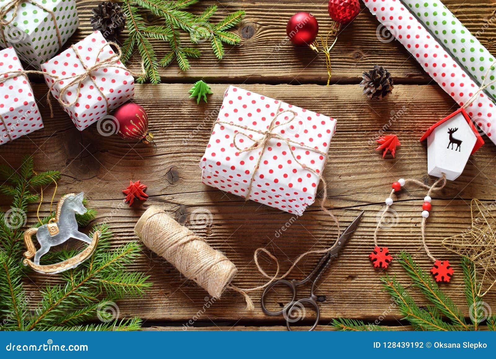 Rött boxas med pilbågen Julsammansättning med den närvarande asken, emballagepapper, festlig garnering och granträdfilialen Förbe