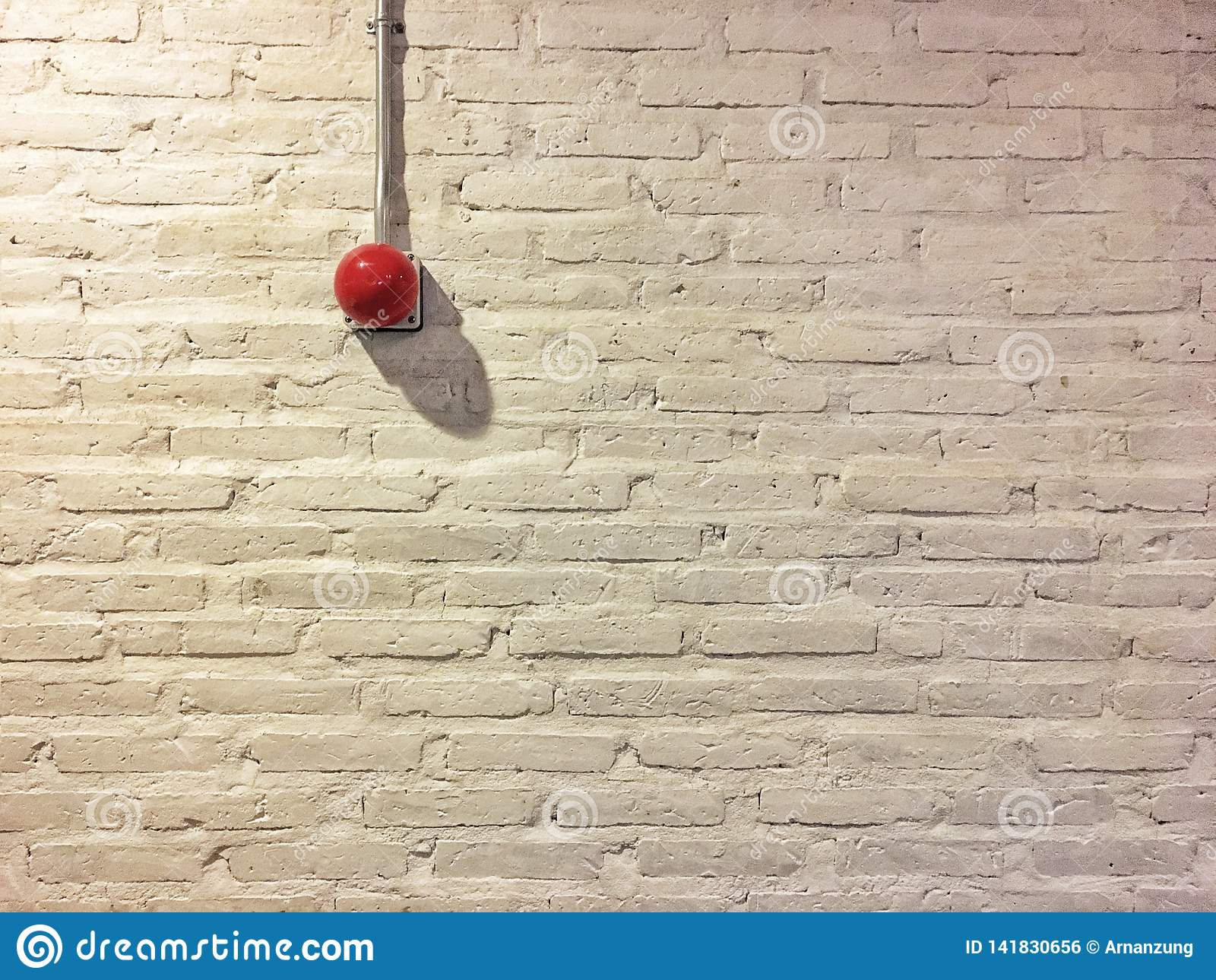 Rött cirkelbrandlarm på den vita tegelstenväggen för tappning