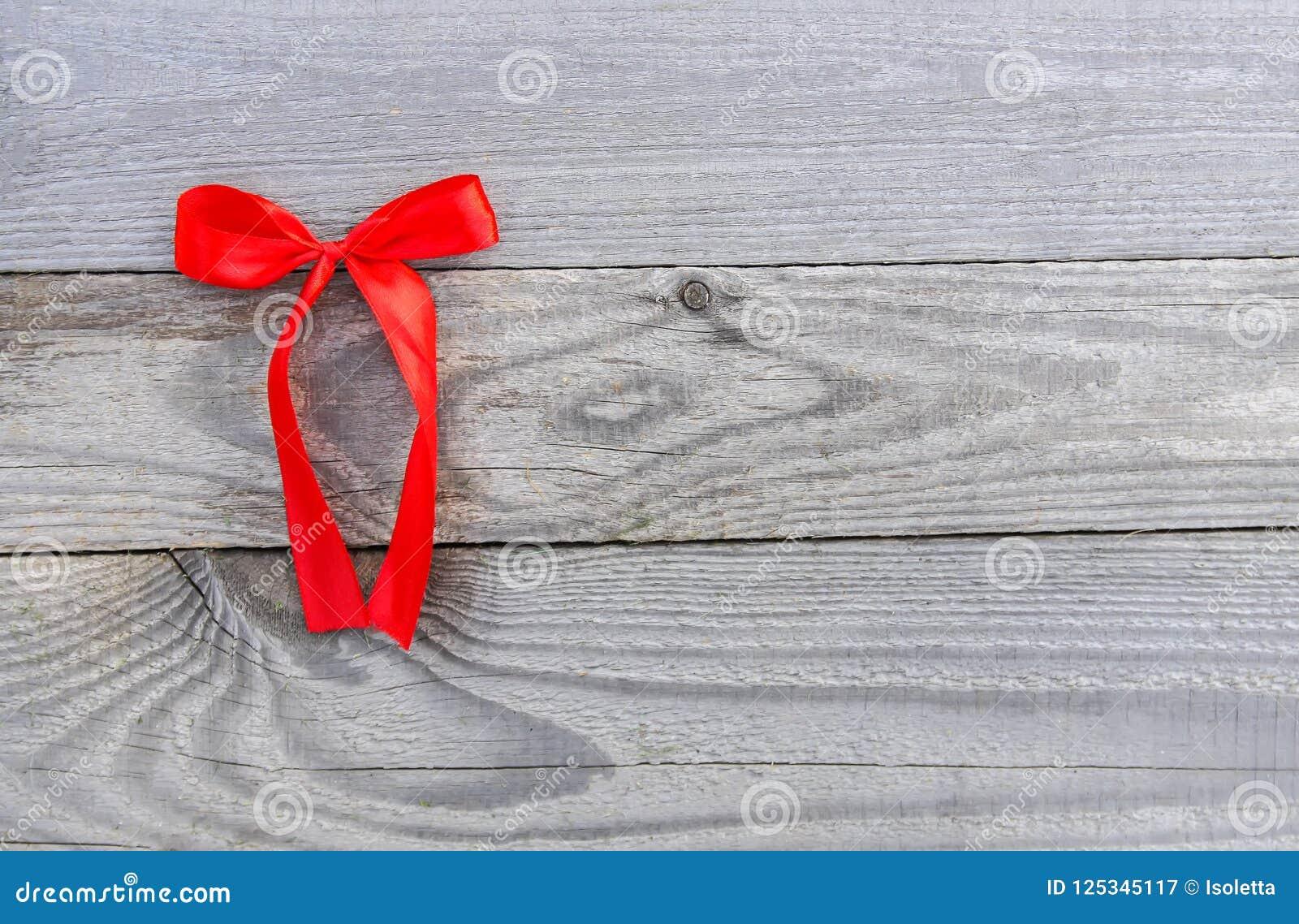 Rött dekorativt band med pilbågen på gammal träbrädebakgrund