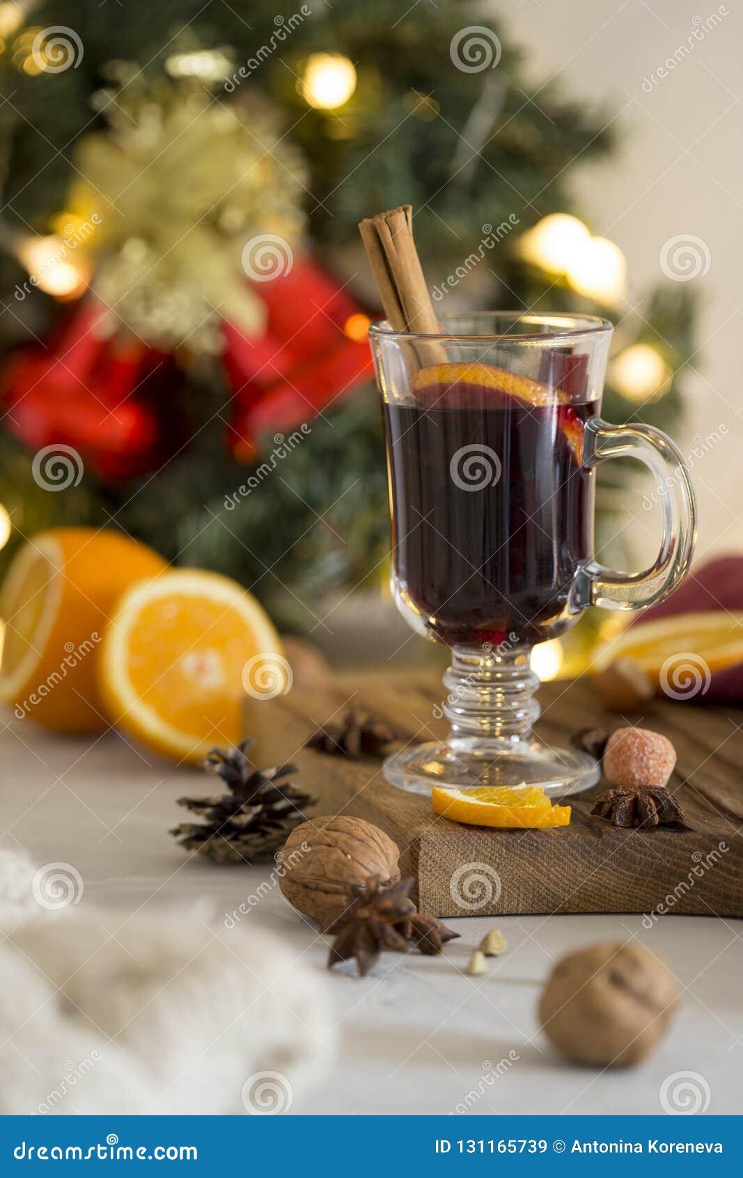 Rött funderat vin för jul i exponeringsglas på träbräde på vit bakgrund
