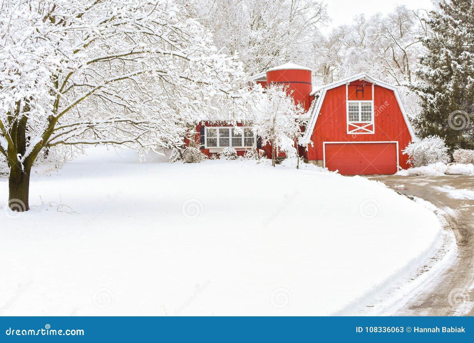 Rött ladugårdhus i en vinterunderland