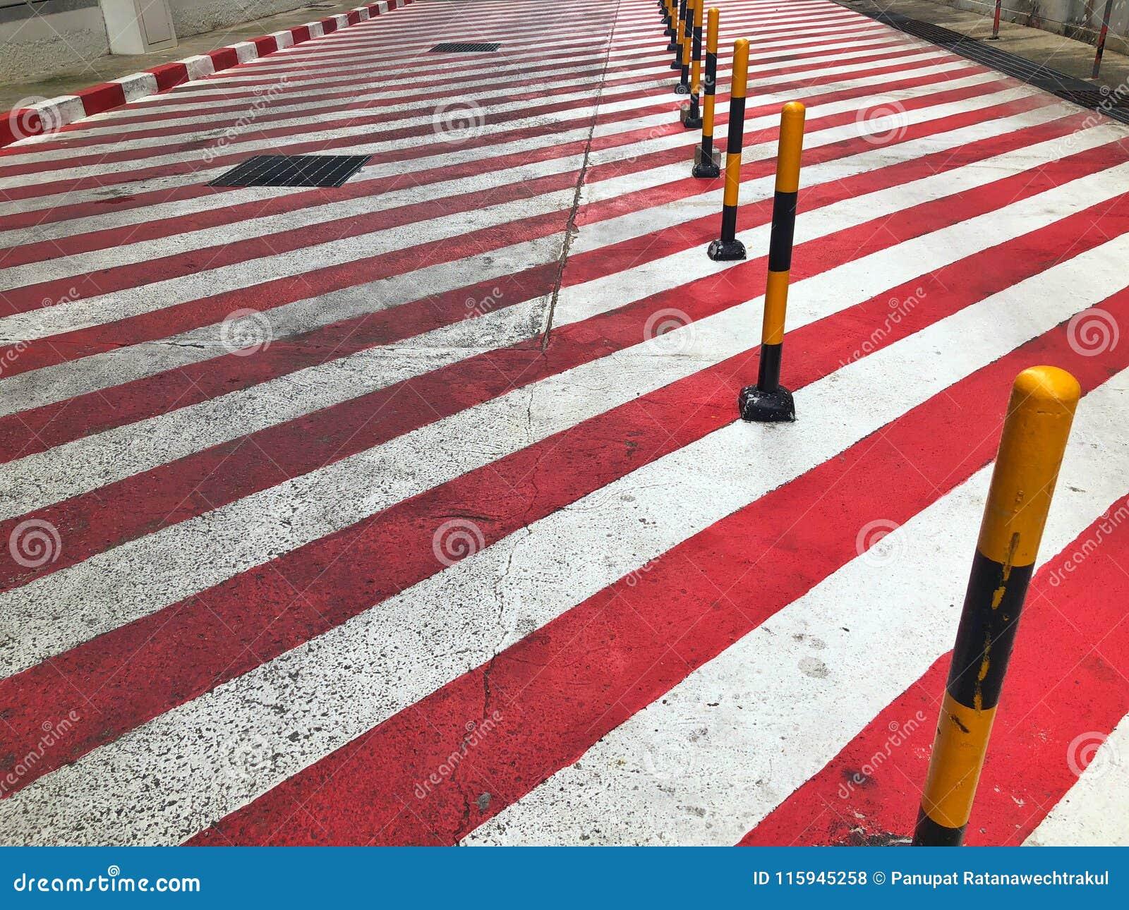 Rött och vitt tecken med guling- och svartstolpen för inget parkeringsområde