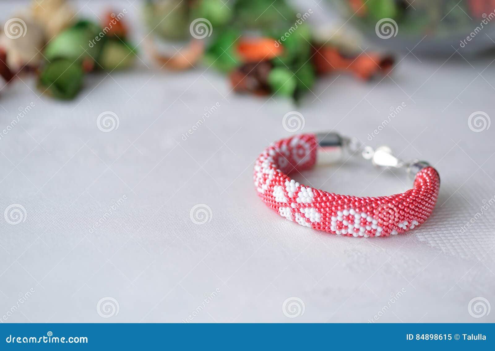 Rött prytt med pärlor virkat armband med det blom- trycket