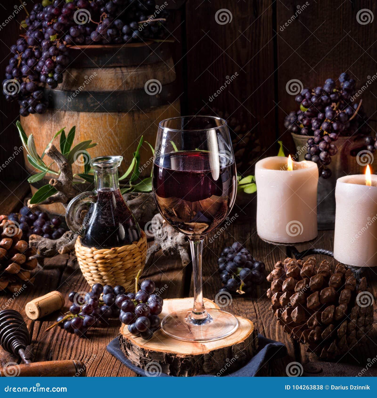 Rött vin från en trumma med druvor och ett exponeringsglas av vin