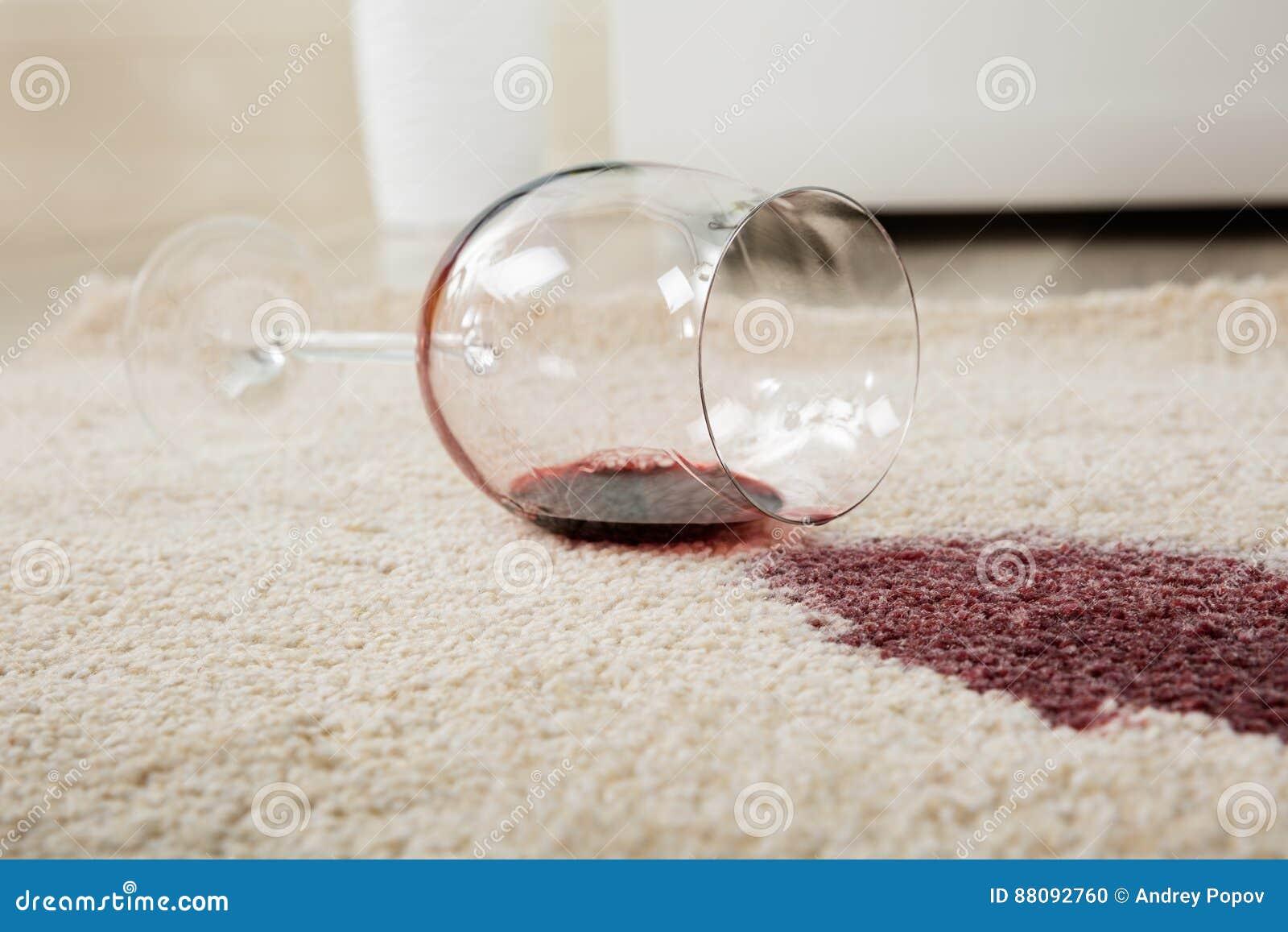 Rött vin som spills från exponeringsglas på matta