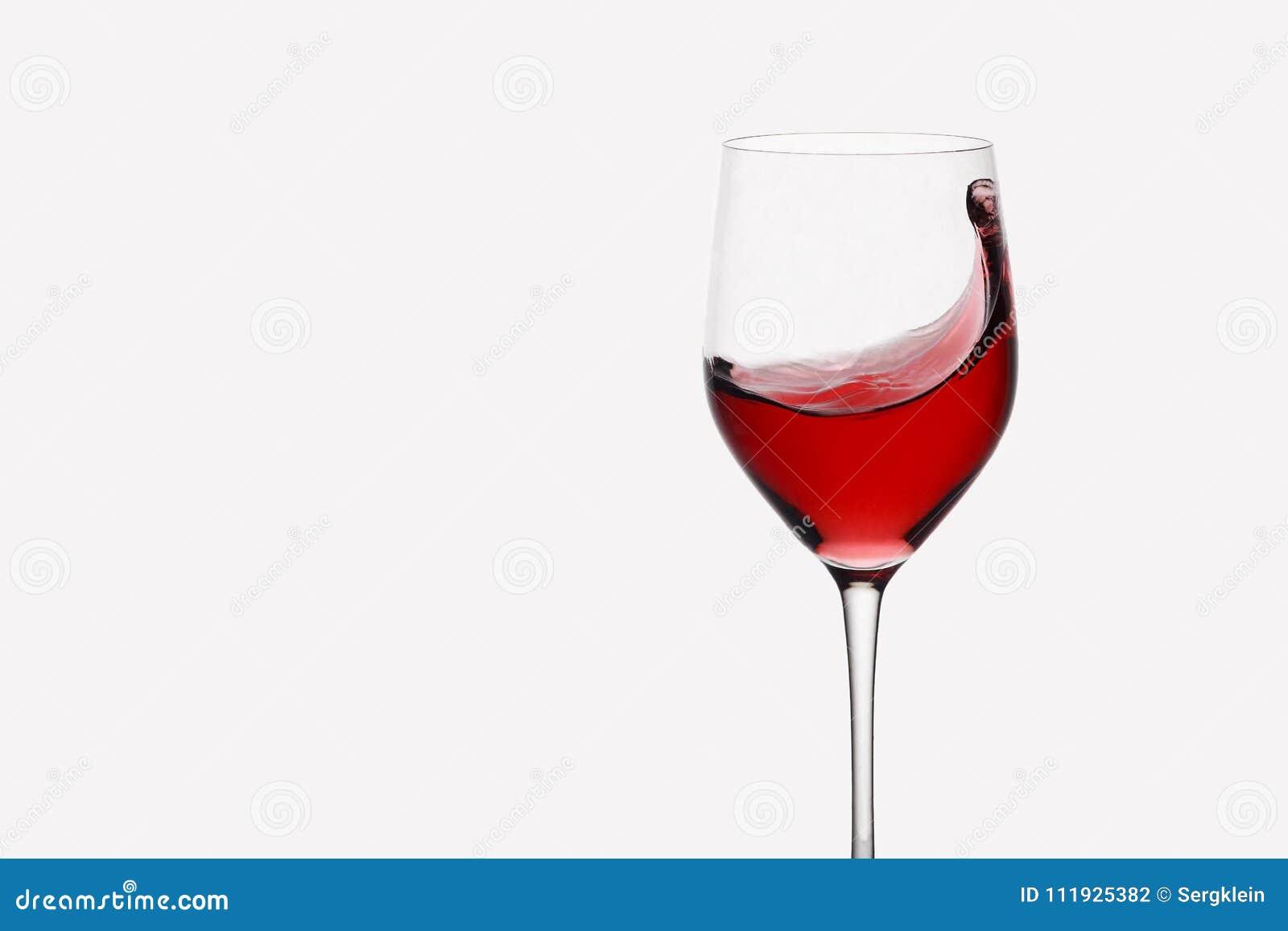 Rött vin som virvlar runt i ett anseende för vinexponeringsglas mot ljus bakgrund