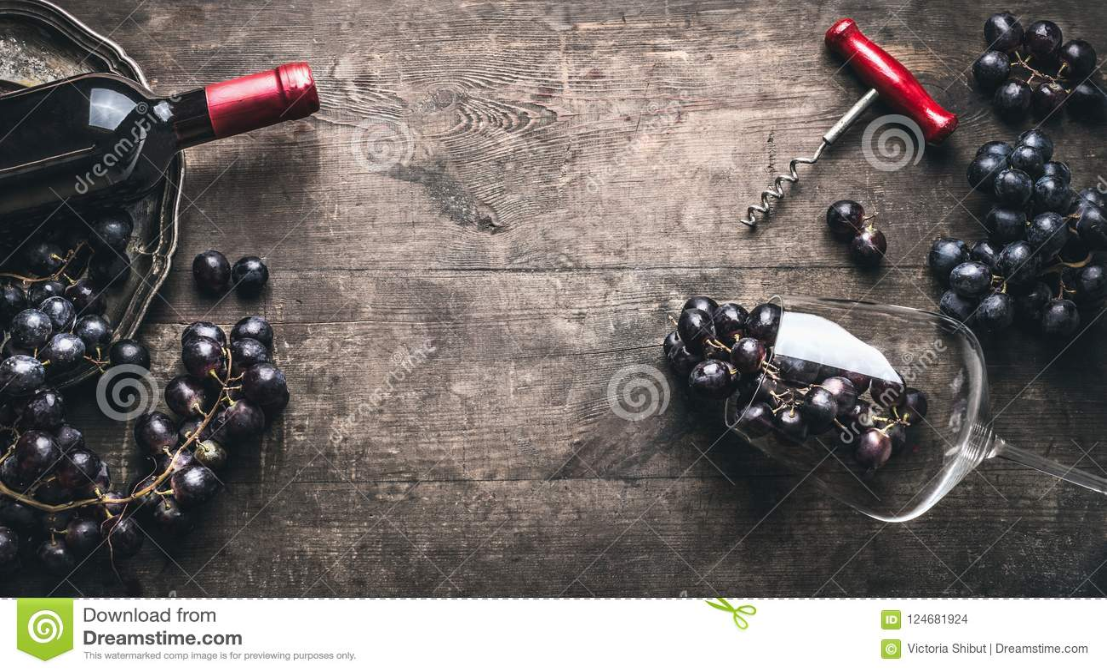 Rött vinbakgrund med flaskan och korkskruv, druvor och vinexponeringsglas på trämörk tappning