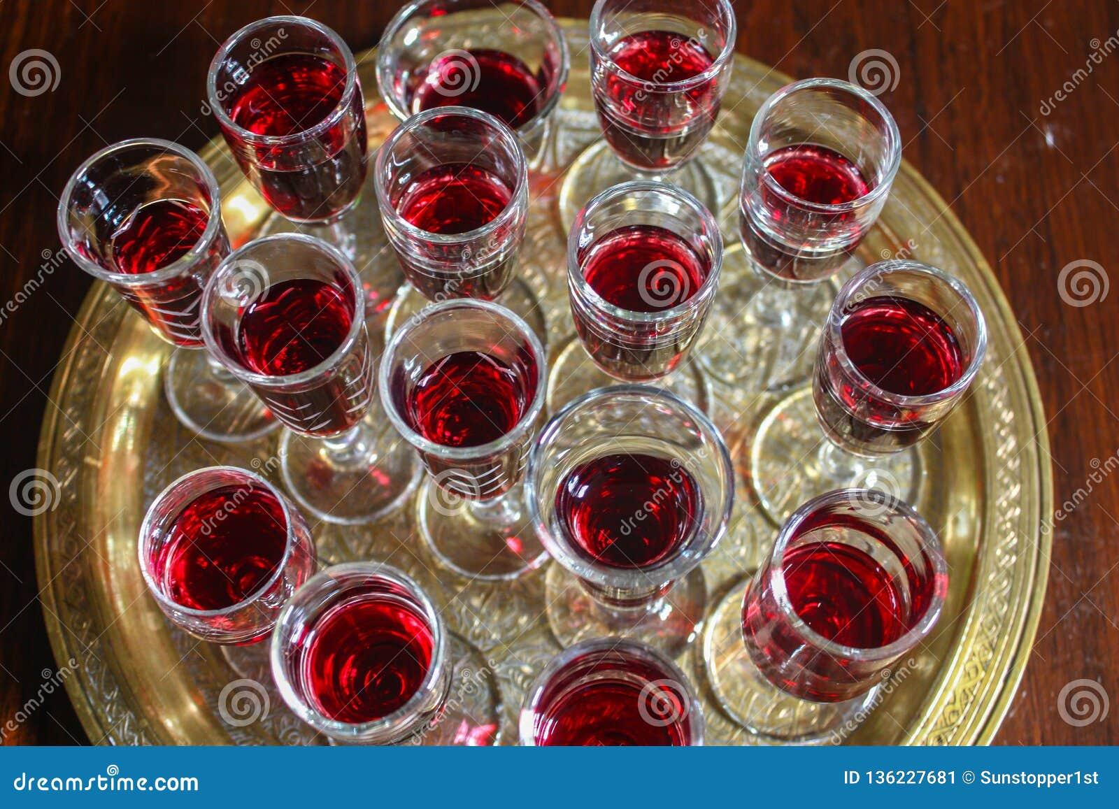 Rött vinexponeringsglas på ett guld- magasin