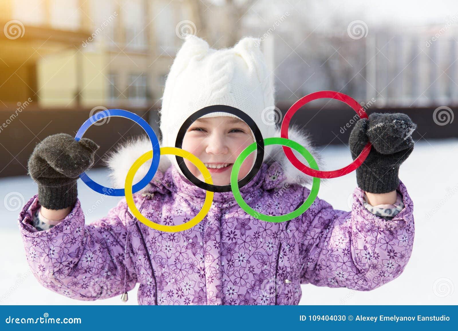 Rússia, cidade de Yasny, região de Orenburg, pista de gelo da escola, 12-10 Anéis olímpicos nas mãos de uma menina bonita