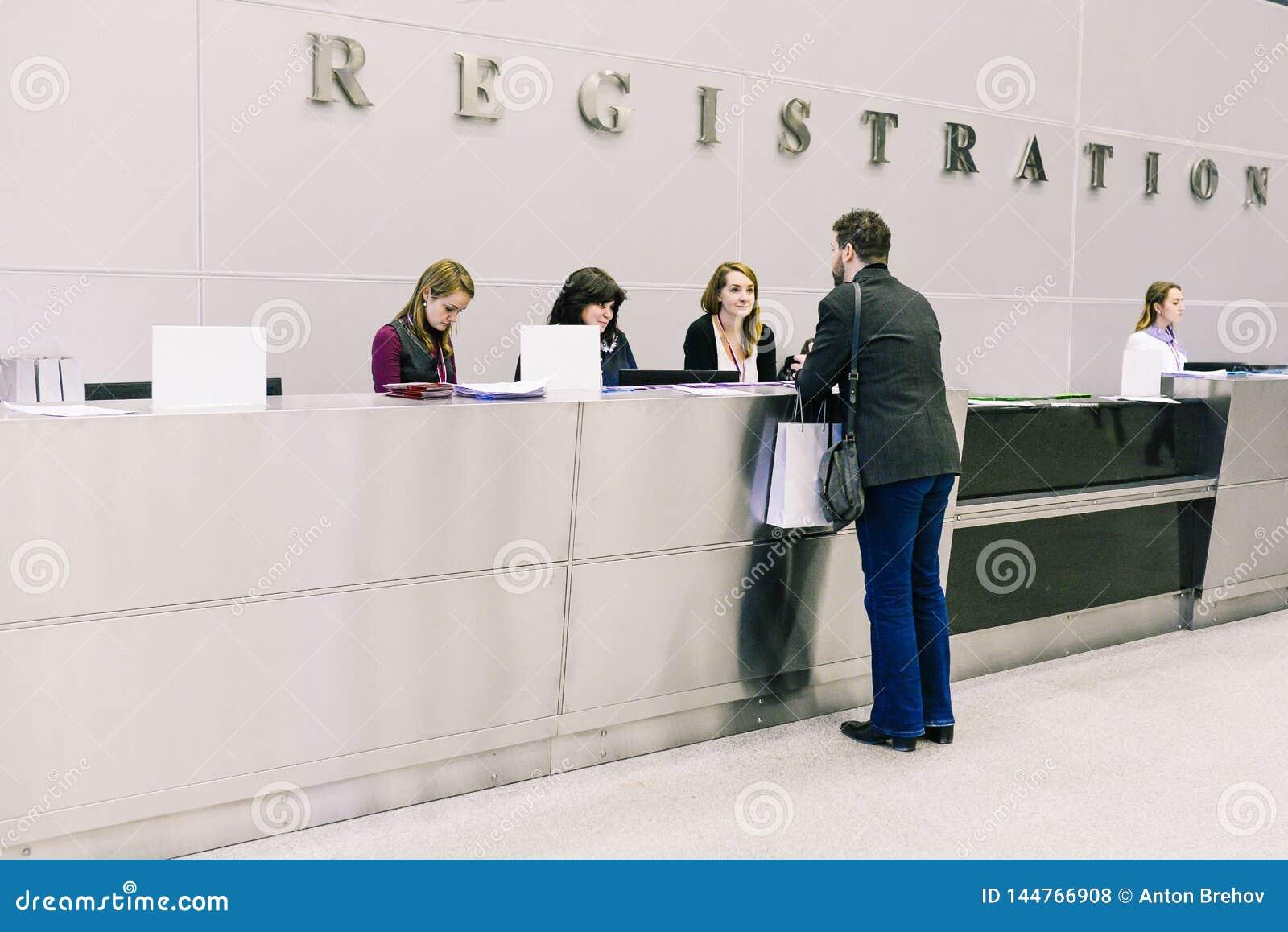 Rússia, cidade Moscou - 18 de dezembro de 2017: O homem na recepção ou no hotel, no escritório ou no aeroporto As meninas dã