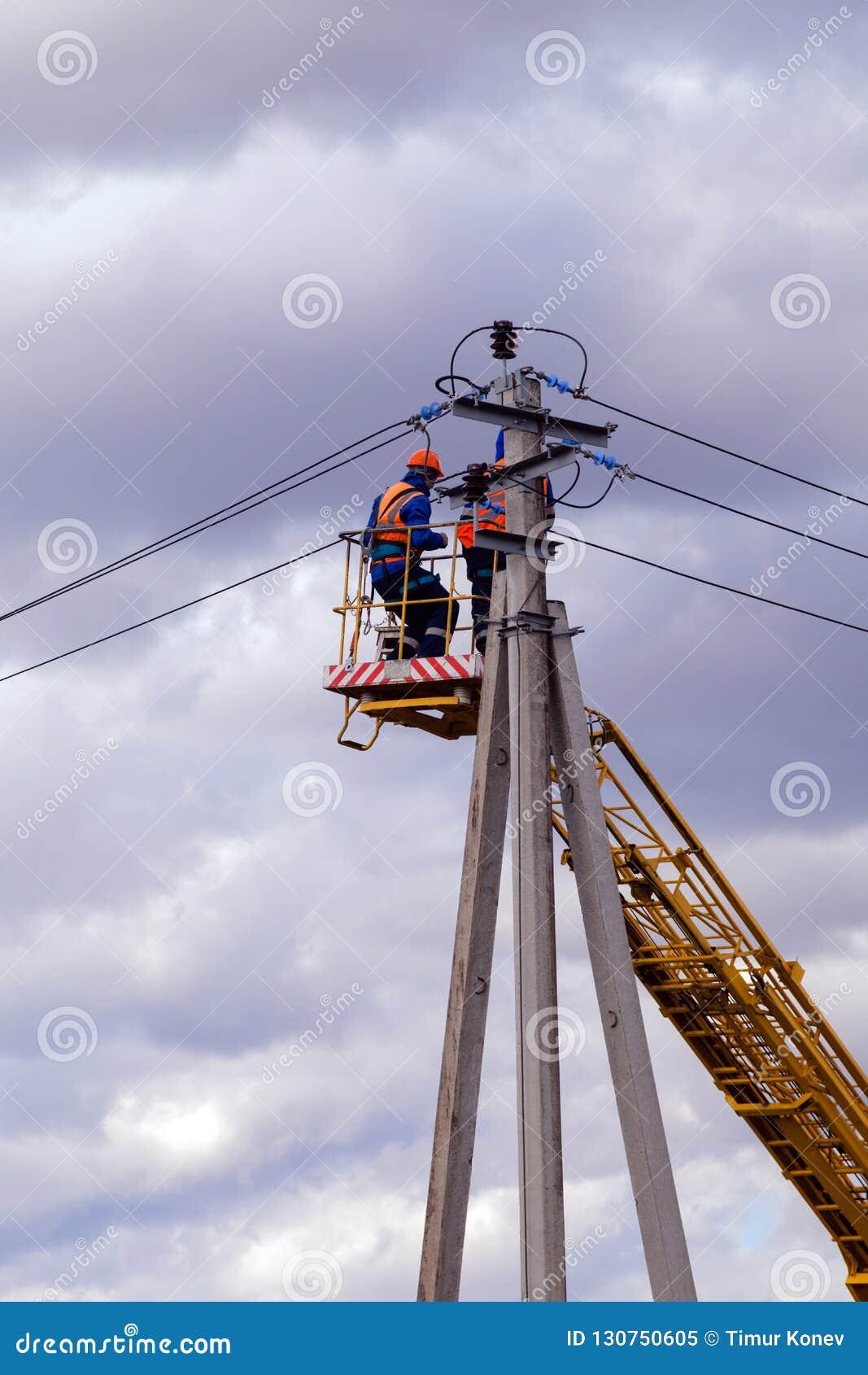 Rússia, Kemerovo, equipe dos eletricistas nos capacetes e nos uniformes r