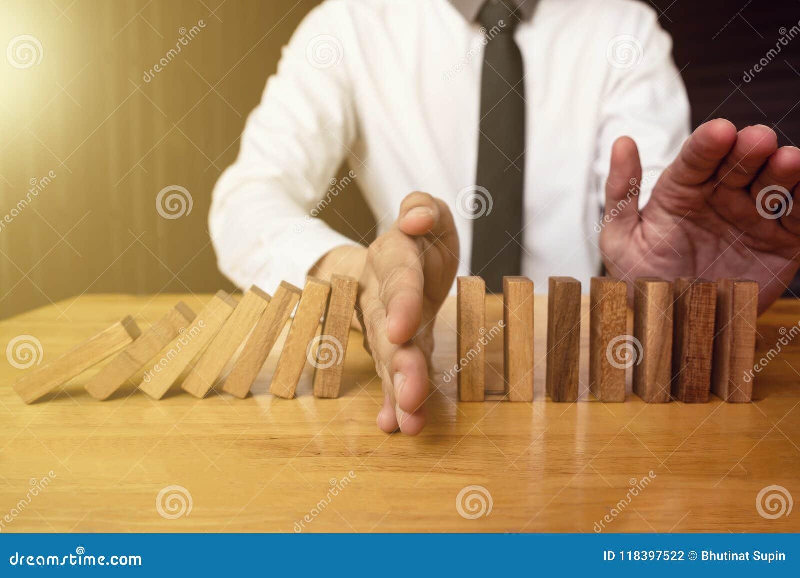 Ręka biznesmen stoping spada drewnianego domino skutek od