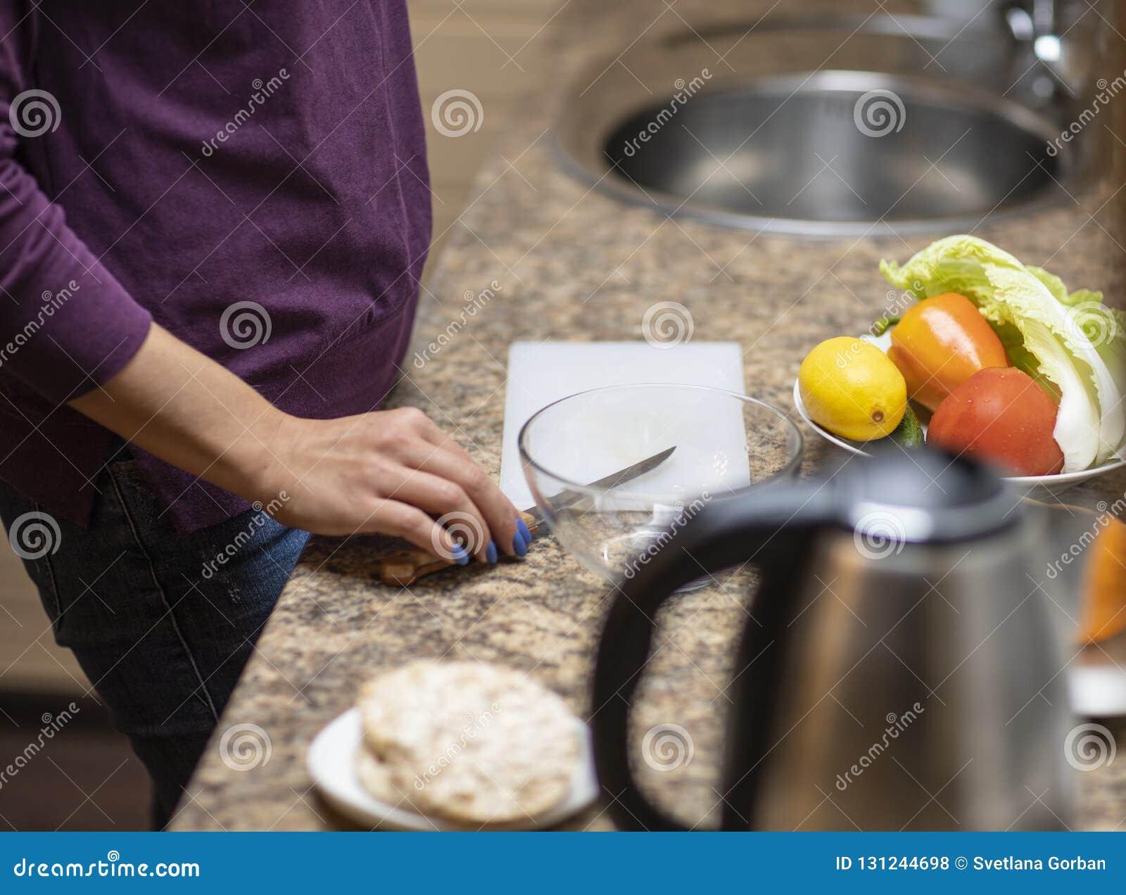 Ręka ciie warzywa dla sałatki w kuchni