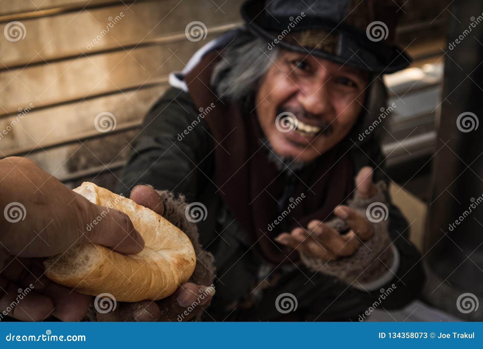 Ręka daje chlebowi lub jedzeniu robić głodnego bezdomnego mężczyzny mieć szczęśliwą twarz