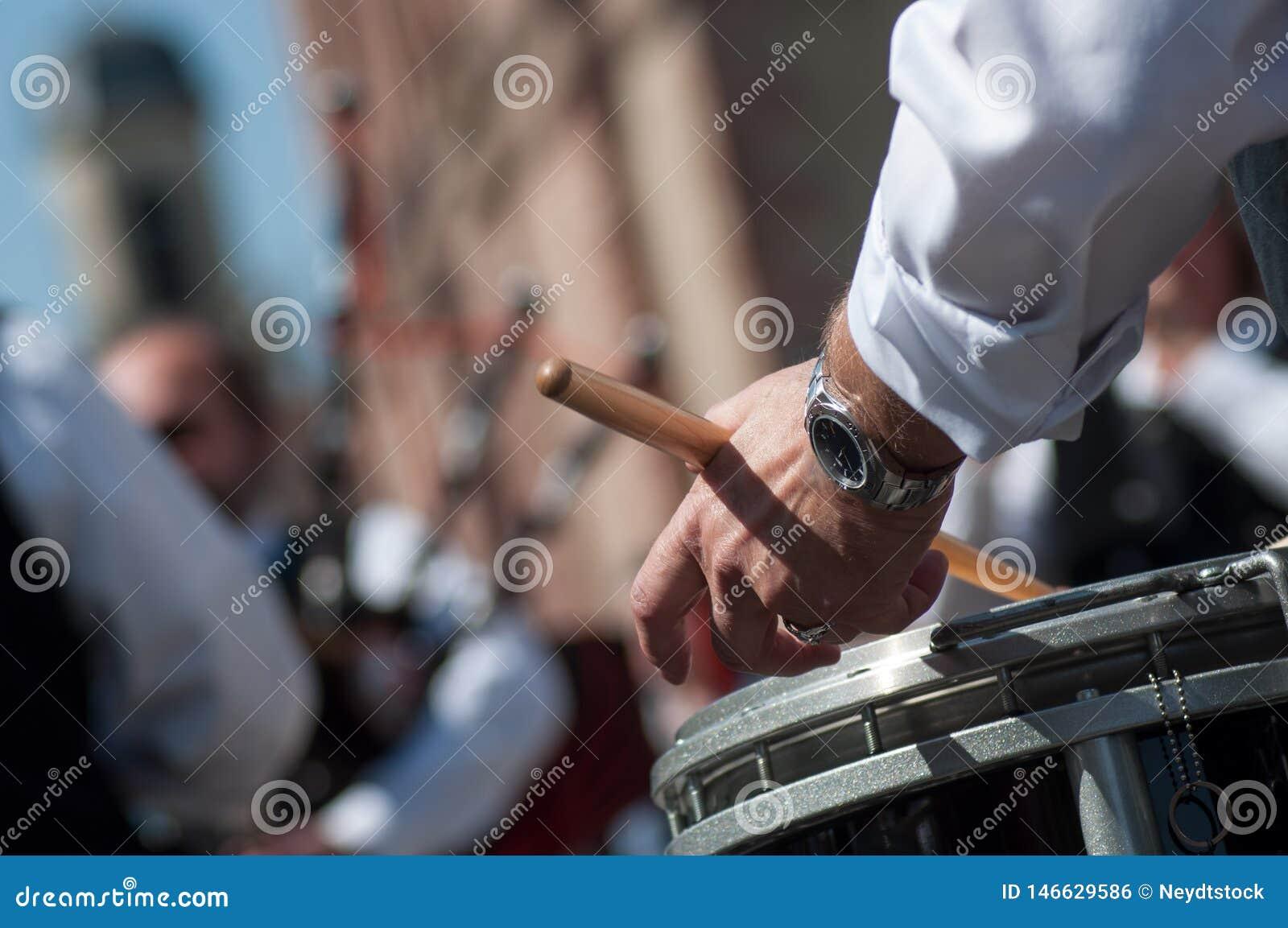 Ręka dobosz w szkockim zespole bawić się w ulicie