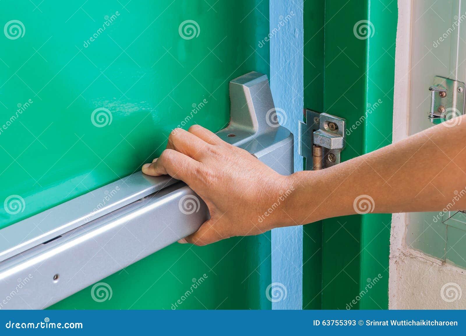 Ręka jest pchać/otwiera przeciwawaryjnego pożarniczego wyjścia drzwi