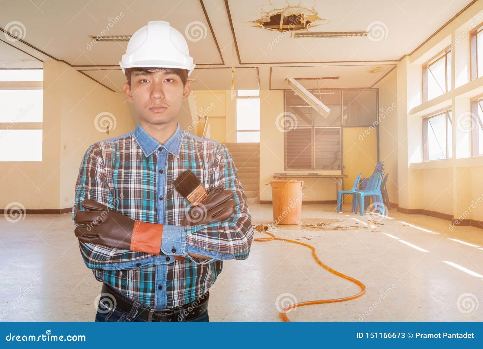 Ręka krzyż inżyniera mienia farby muśnięcie w zatrudnienie naprawy wody przecieku kropli wn?trza budynku biurowym