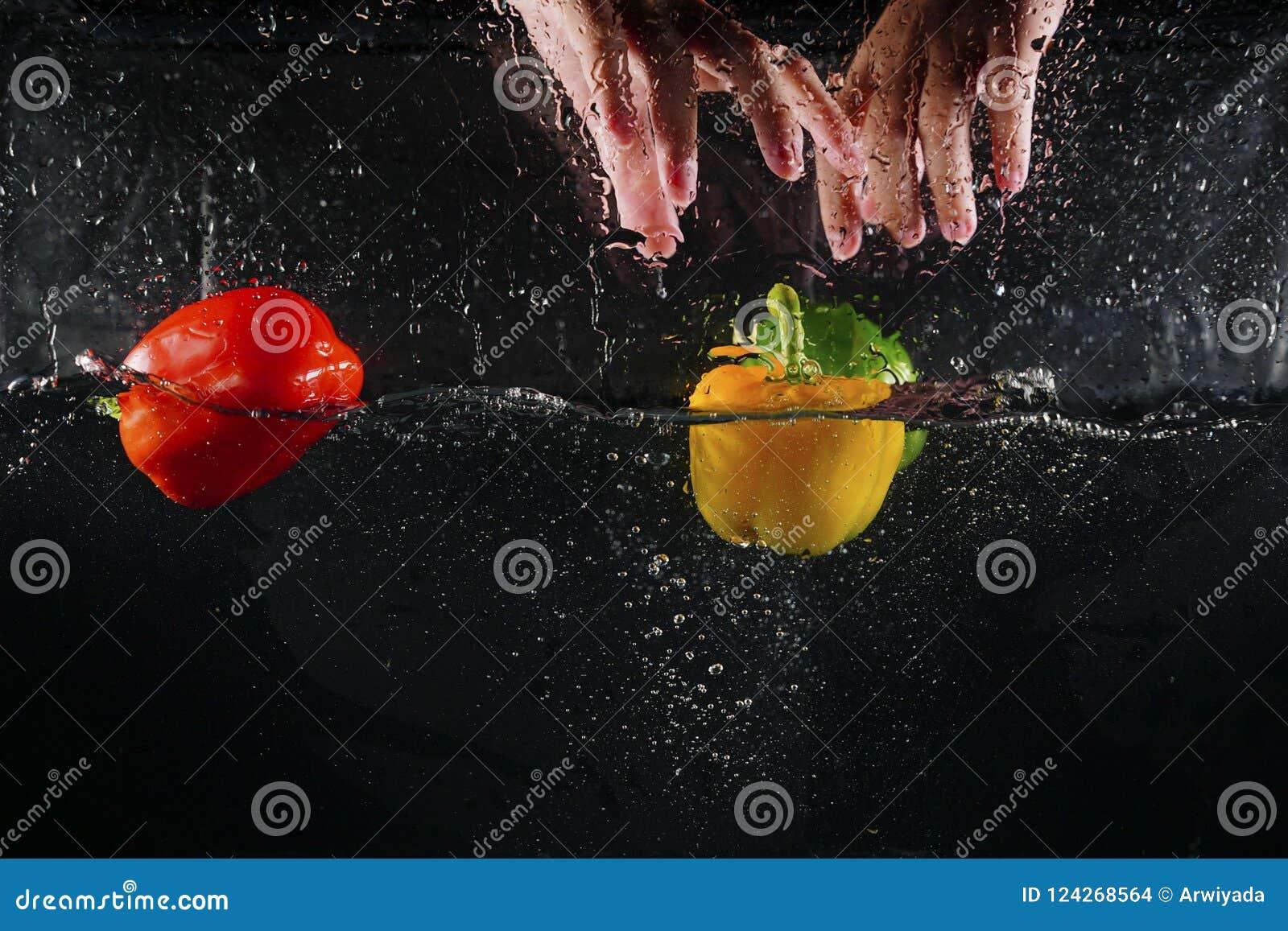 Ręka na górze kilka coloured paprykę spada w wodnych splas