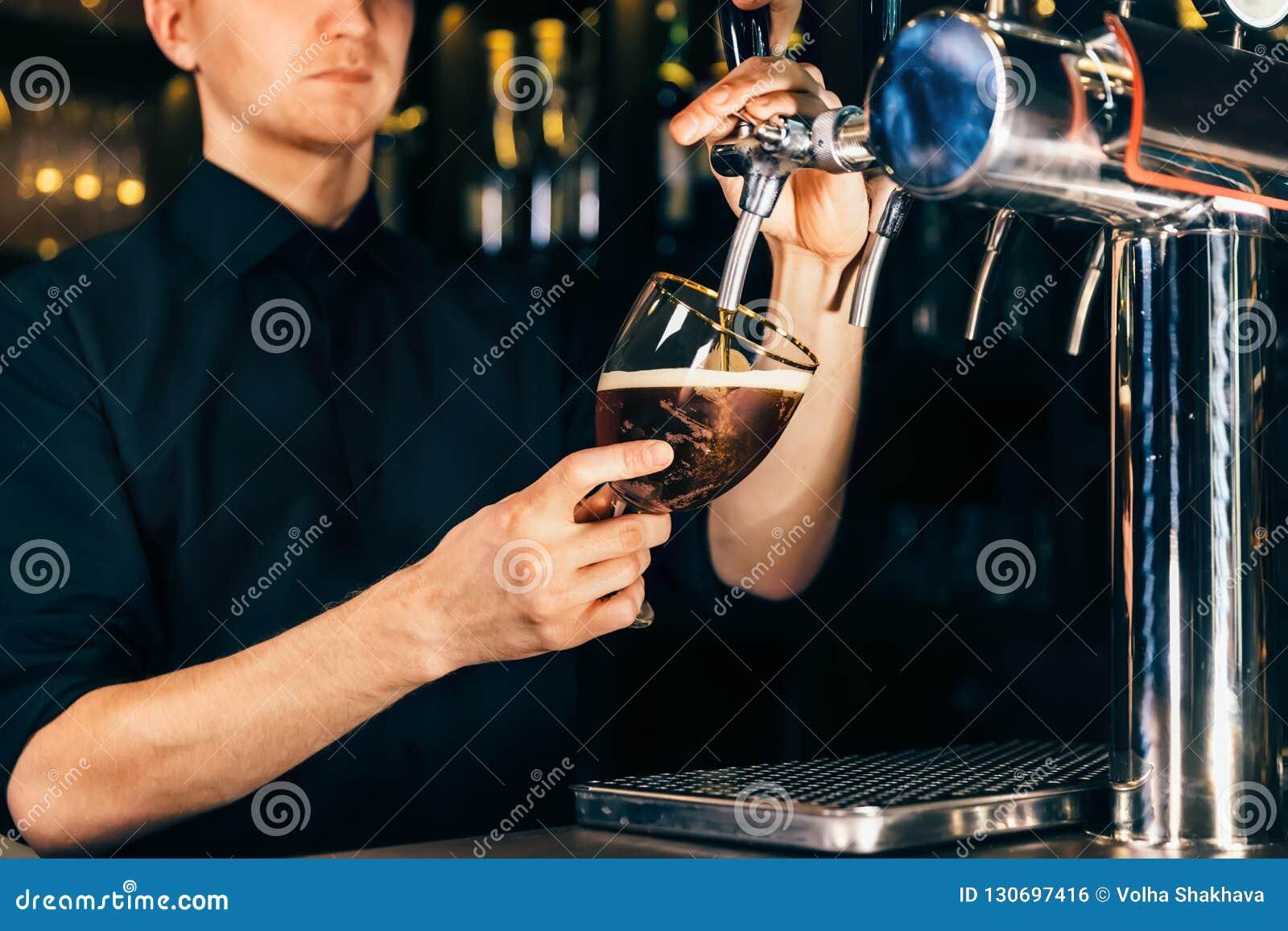 Ręka nalewa wielkiego lager piwo w klepnięciu w pubie lub restauracji barman