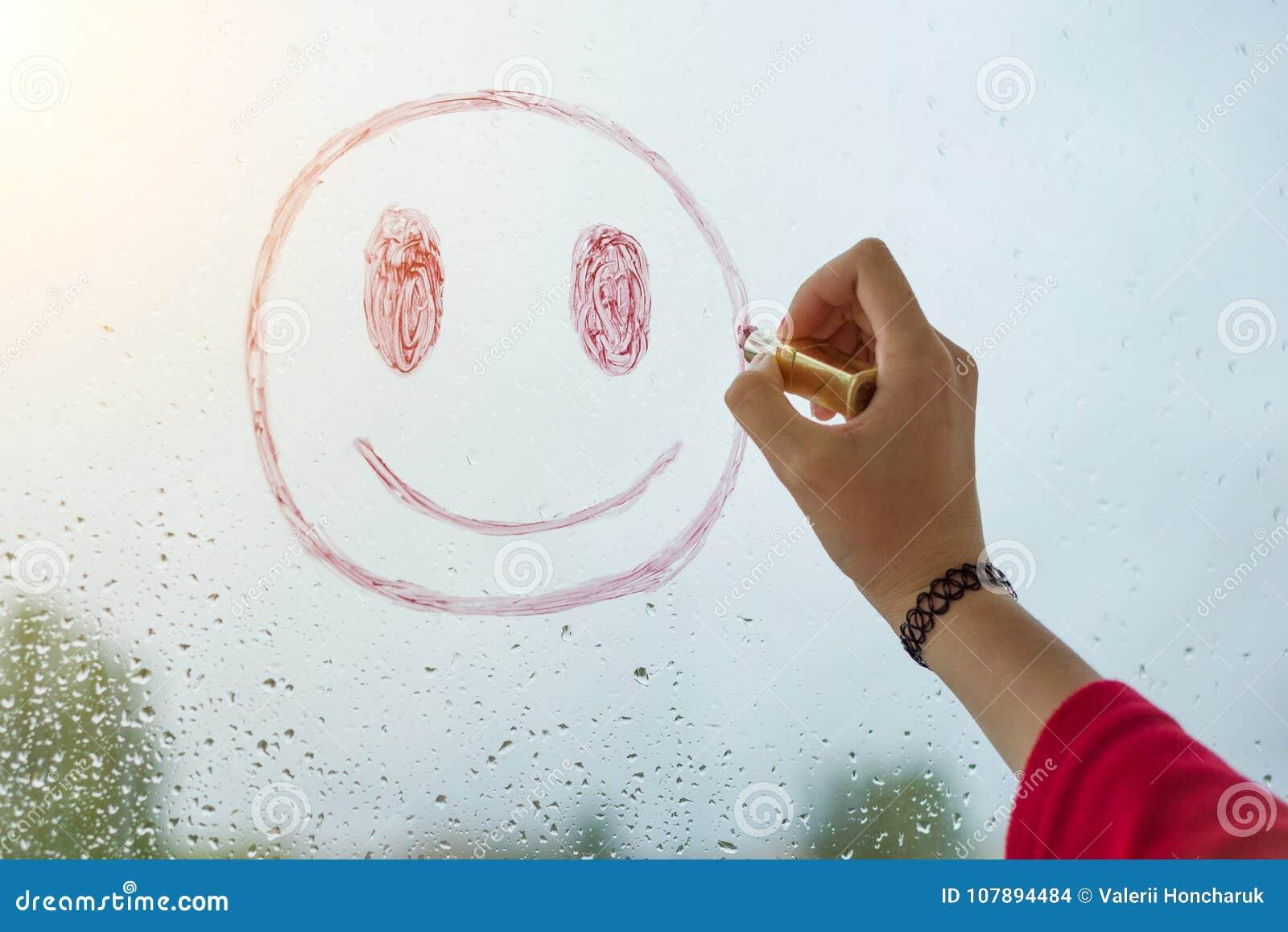 Ręka rysuje pozytywnego smiley na dżdżystym jesieni okno