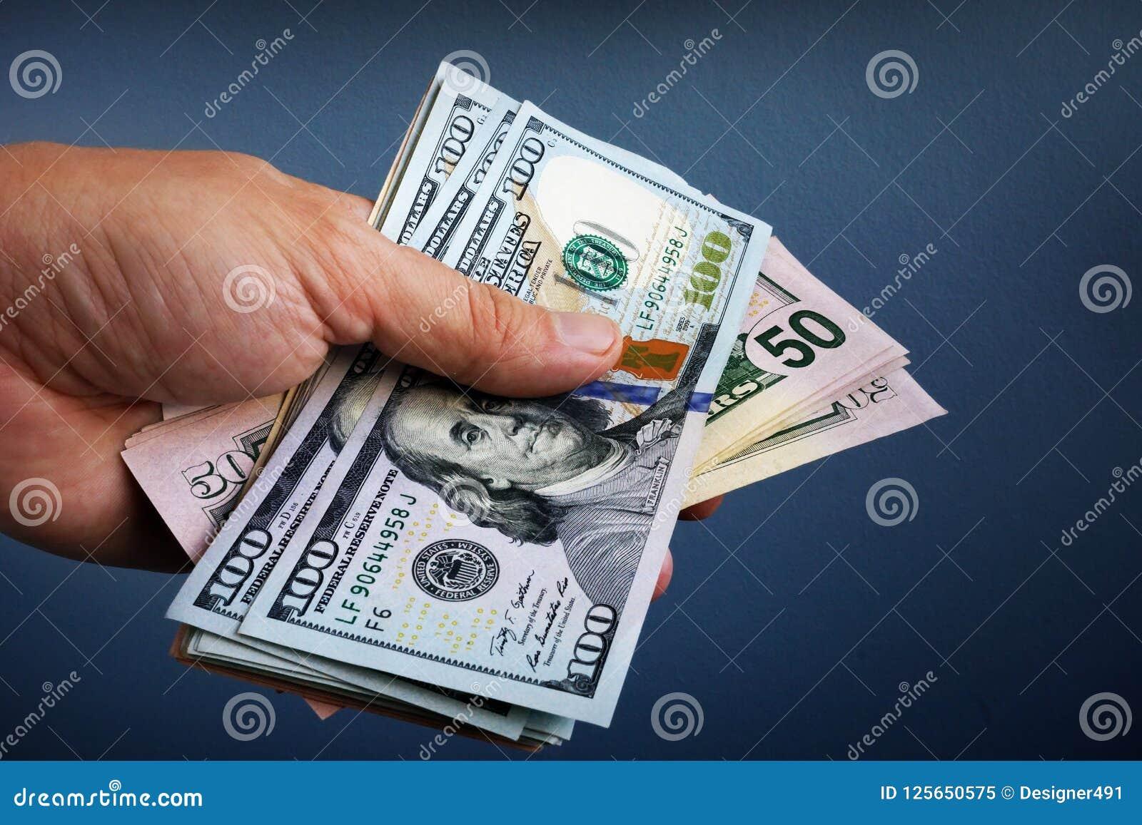 Ręka trzyma dolarowych banknoty Pożyczka i pożyczanie