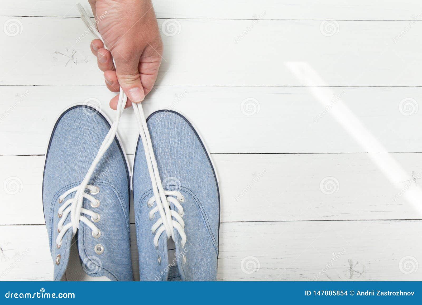 Ręka trzyma niebieskich dżinsów sneakers koronkami na białym drewnianym tle