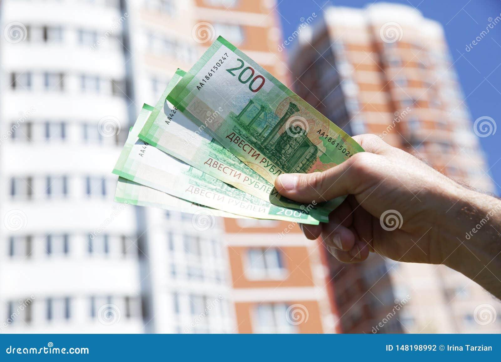 Ręka trzyma nowego Rosyjskiego banknot dwieście rubli na tle duży budynek niebieskie niebo i Got?wkowy papierowy pieni?dze