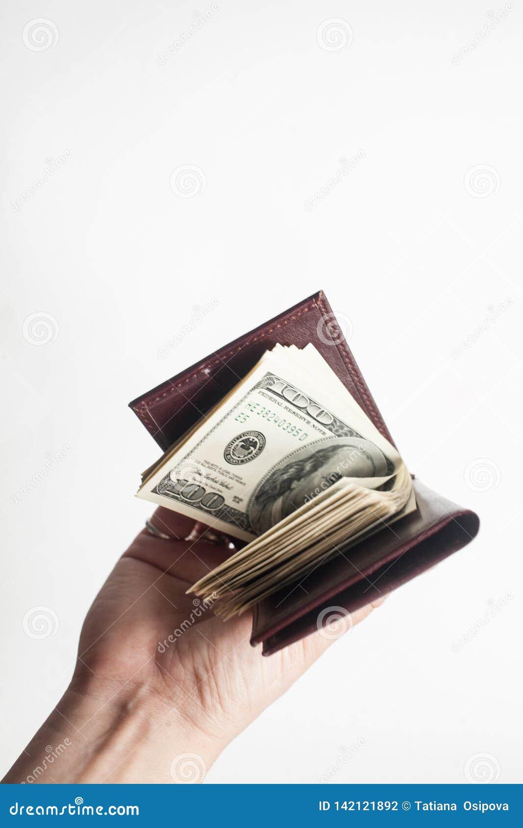 Ręka trzyma portfel sto dolarowych rachunków odizolowywających nad białym tłem pełno pionowo