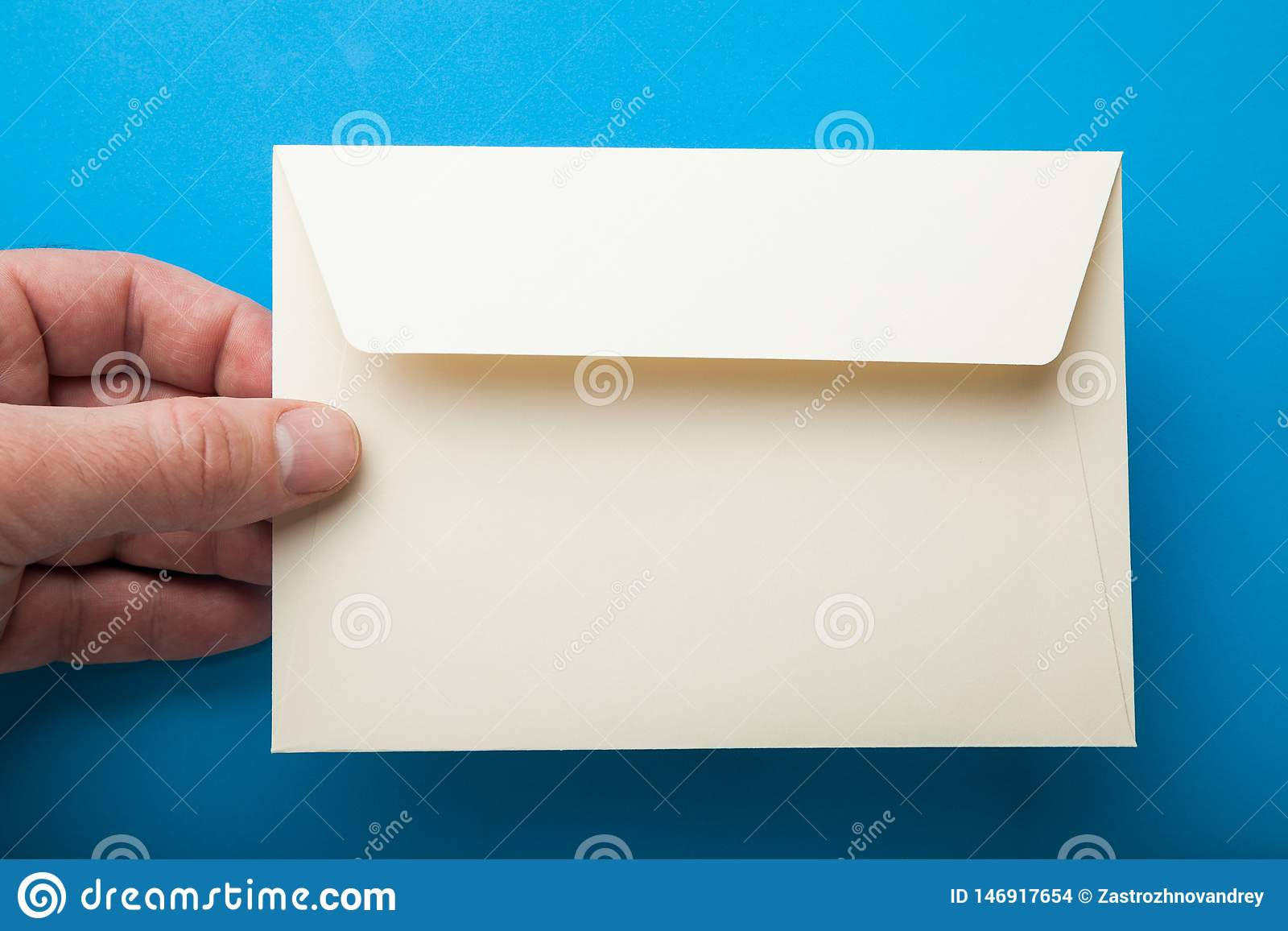Ręka trzyma pustą kopertę na błękitnym tle