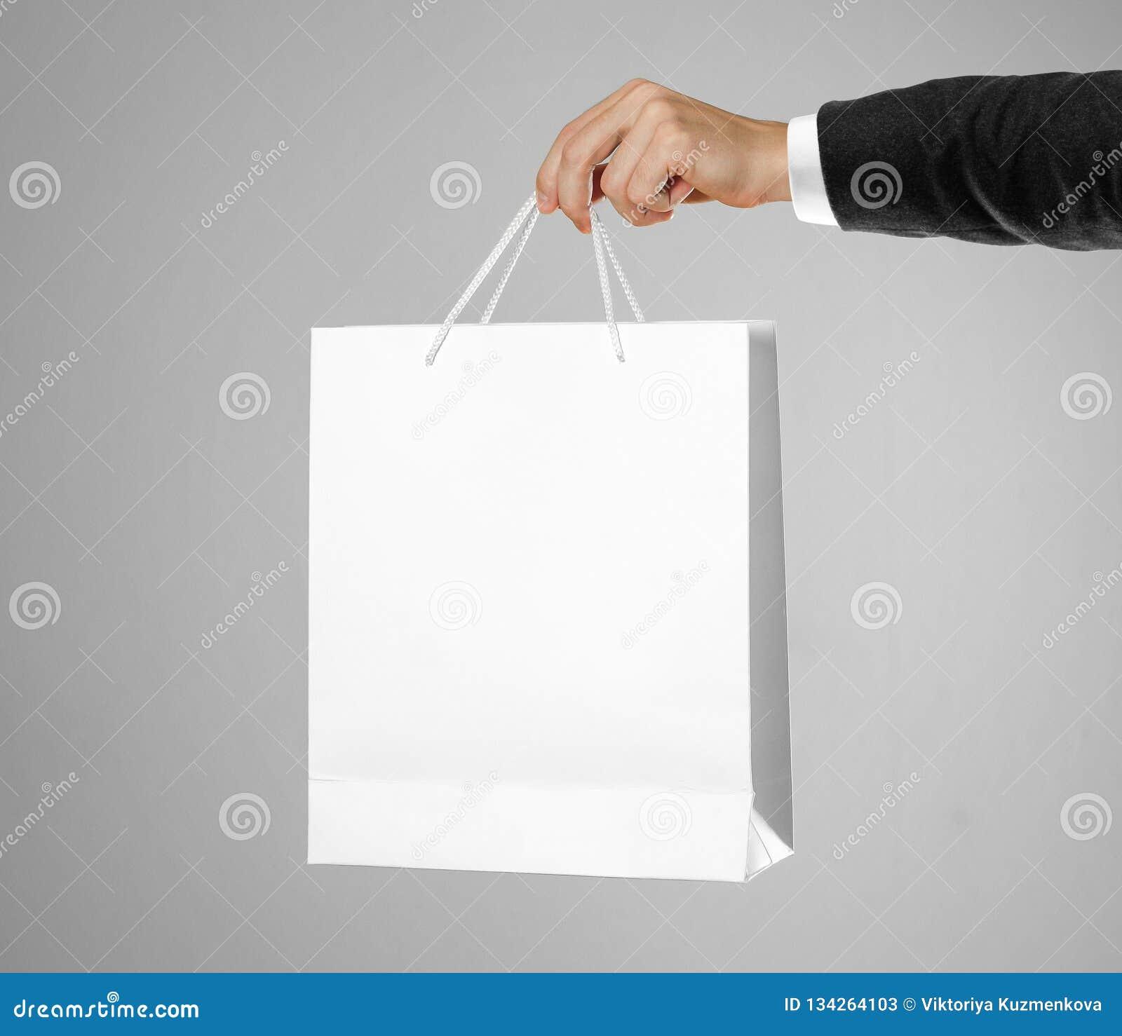 Ręka w białej koszula i czarnej kurtce trzyma białą prezent torbę