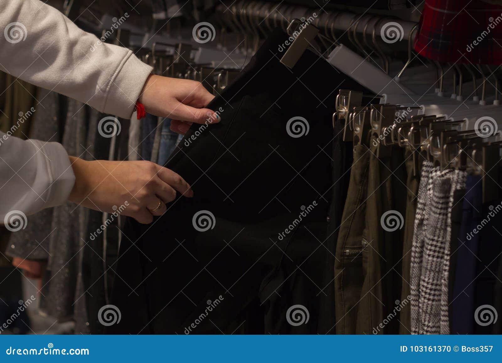 Ręka wyszukuje stojaki spodnia
