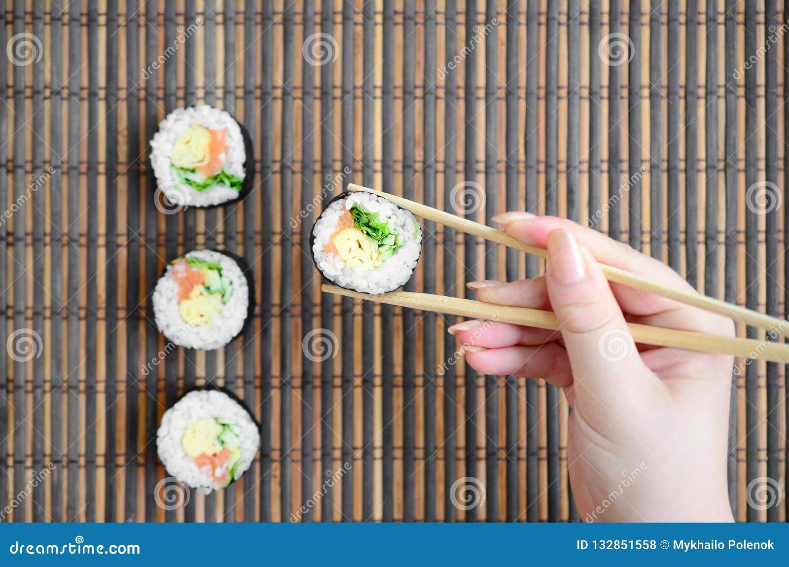 Ręka z chopsticks trzyma suszi rolkę na bambusowym słomianym serwing matowym tle azjatykci jedzenie smażący ryżowi tradycyjni war