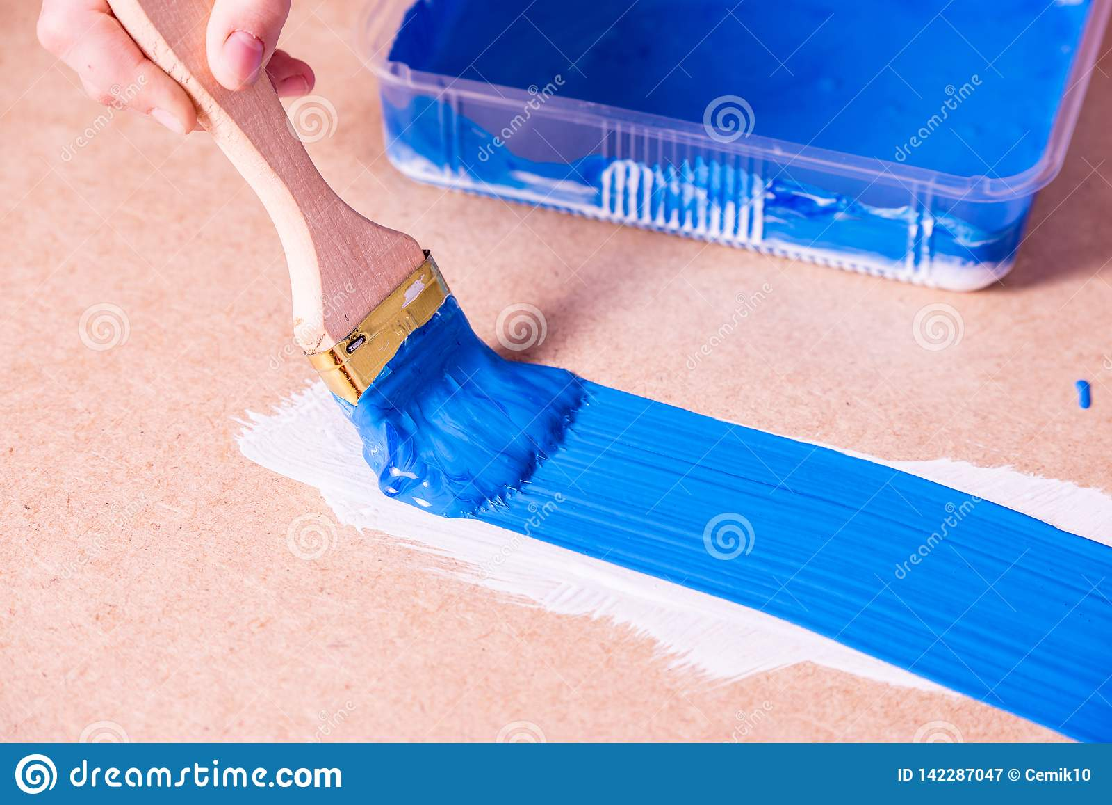 Ręka z muśnięcie farbami z błękitną farbą