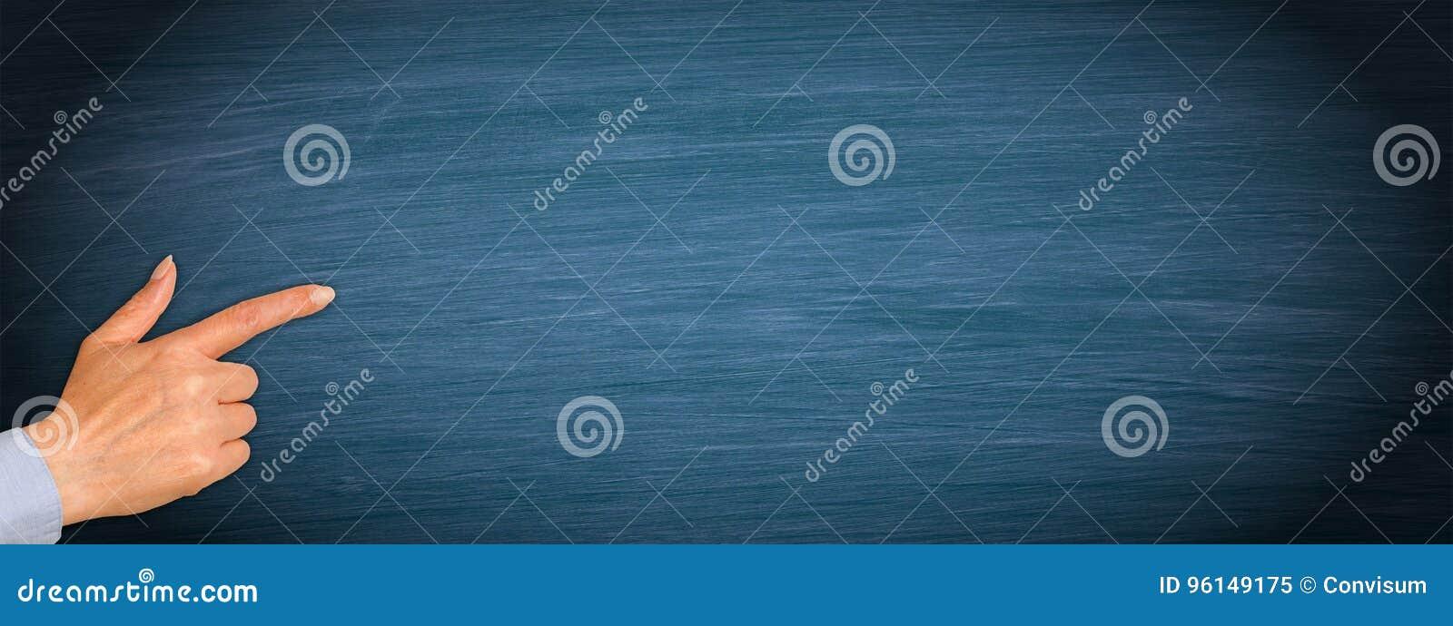 Ręka z palcem wskazującym na pustym błękitnym chalkboard tle