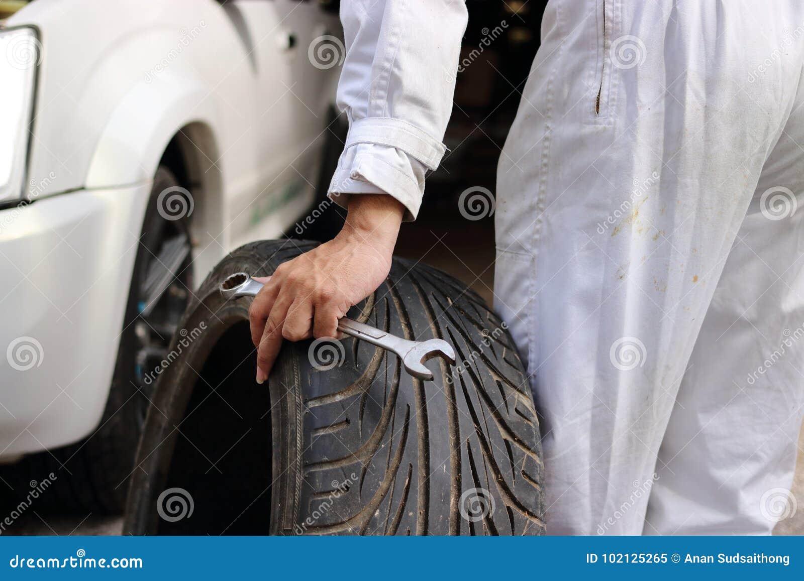 Ręki automobilowy mechanik w mundurze z oponą i wyrwaniem dla załatwiać samochód przy remontowym garażu tłem